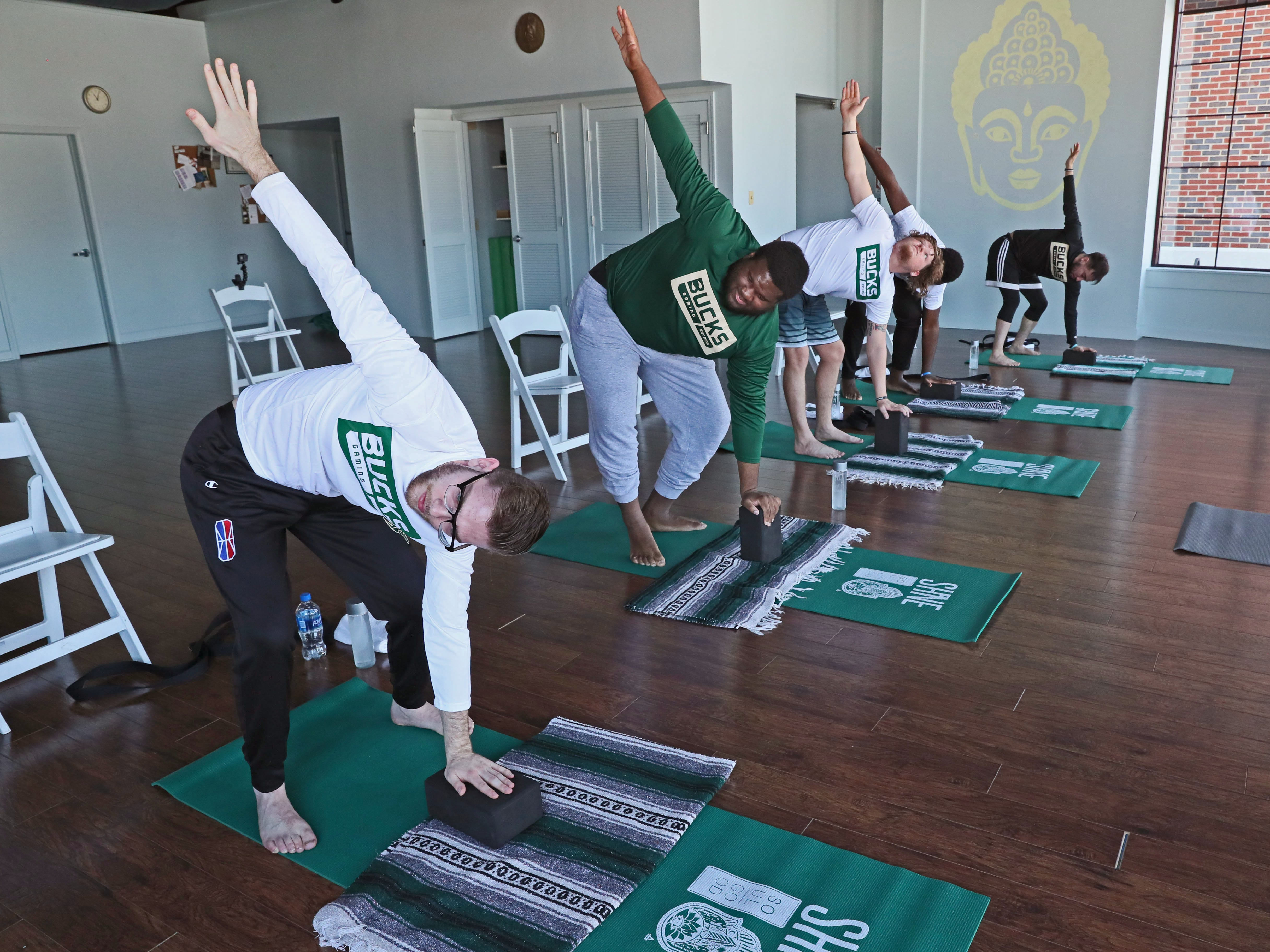"""Team members Stephen Lay (from left), Jovan Tenner, Robert """"Brandon"""" Harter, Aaron Rookwood and Chad Fodderie go through yoga positions."""