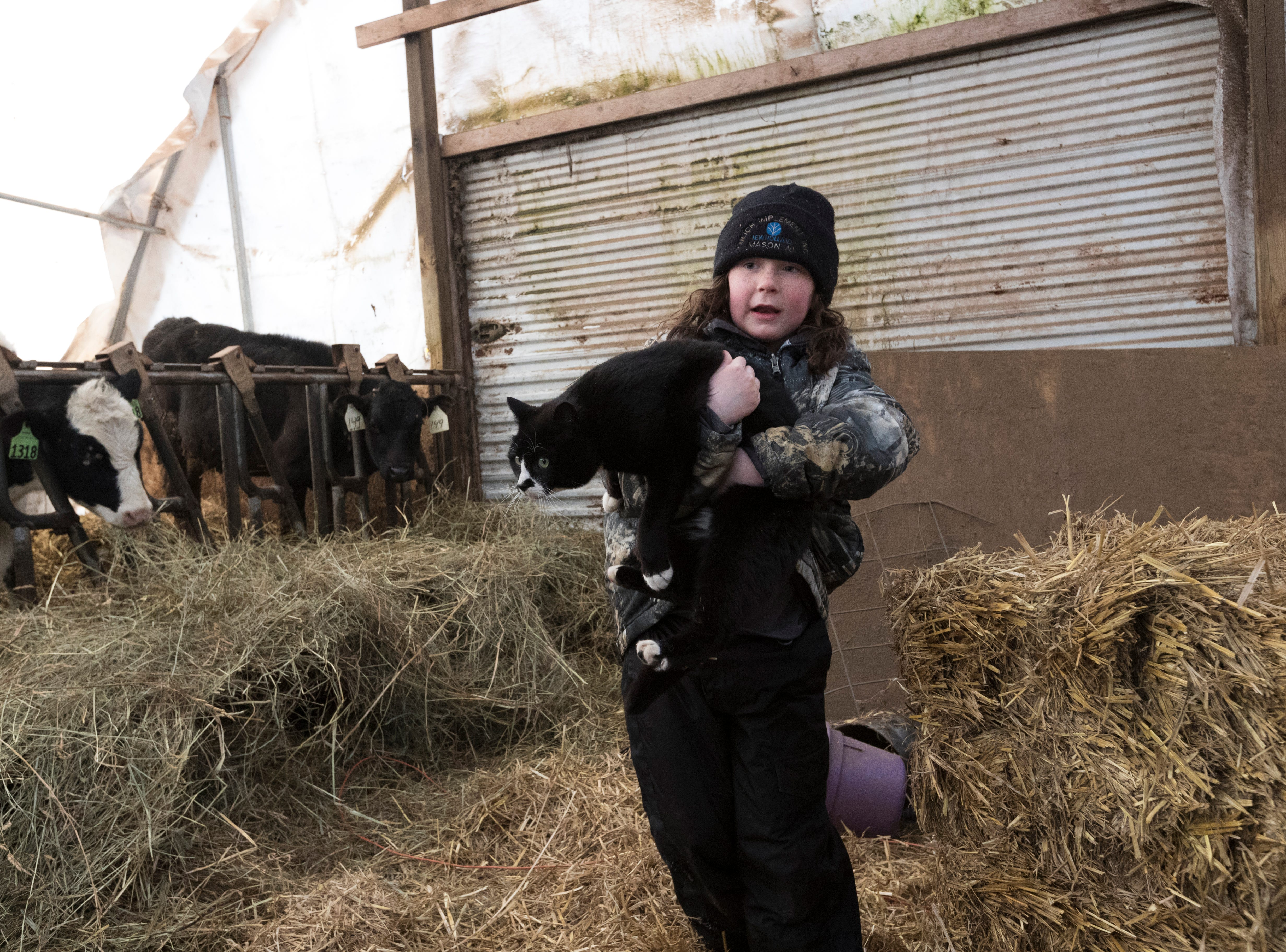 """Starr Thewis carries a cat named """"Precious"""" on her family' farm."""