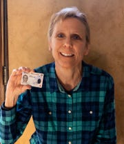Gretchen Schuldt holds up her new driver's license. She has spent the past few months fighting for the legal right to use her birth name on a marriage certificate, Social Security card and driver's license.