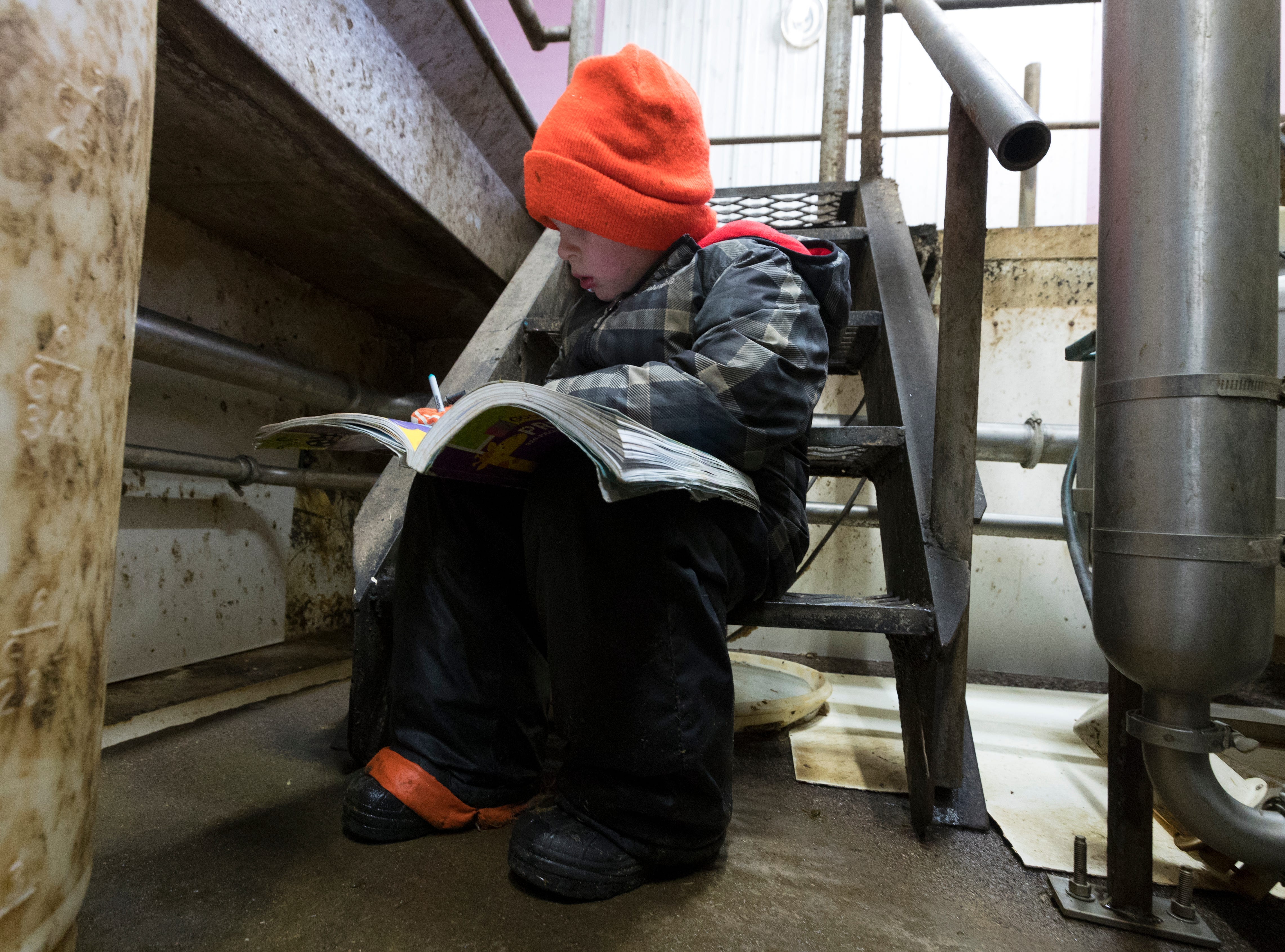 Skyler Thewis writes in a workbook while  his parents work in the milking parlor.