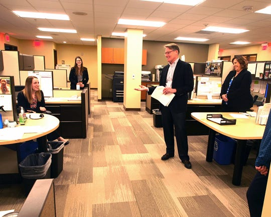 Mark W. Mohr, CEO of First Bank Financial Centre, celebrates the work anniversary date of Kayla Schroeder while employees Melissa Scheid-Grosjean and Kim Berger (right) watch.