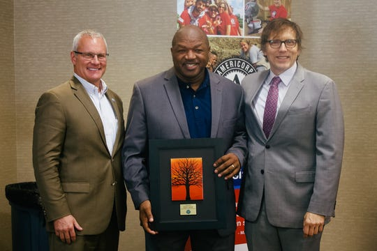 Eldonta Osborne (center) recently was named the national recipient of the Boys & Girls Club's Herman S. Prescott Award. Osborne was presented the award by Drake Mills (left), president of the North Central Boys & Girls Club Board, and Joe Ethier (right) Director of Organizational Development for Boys & Girls Club of America.