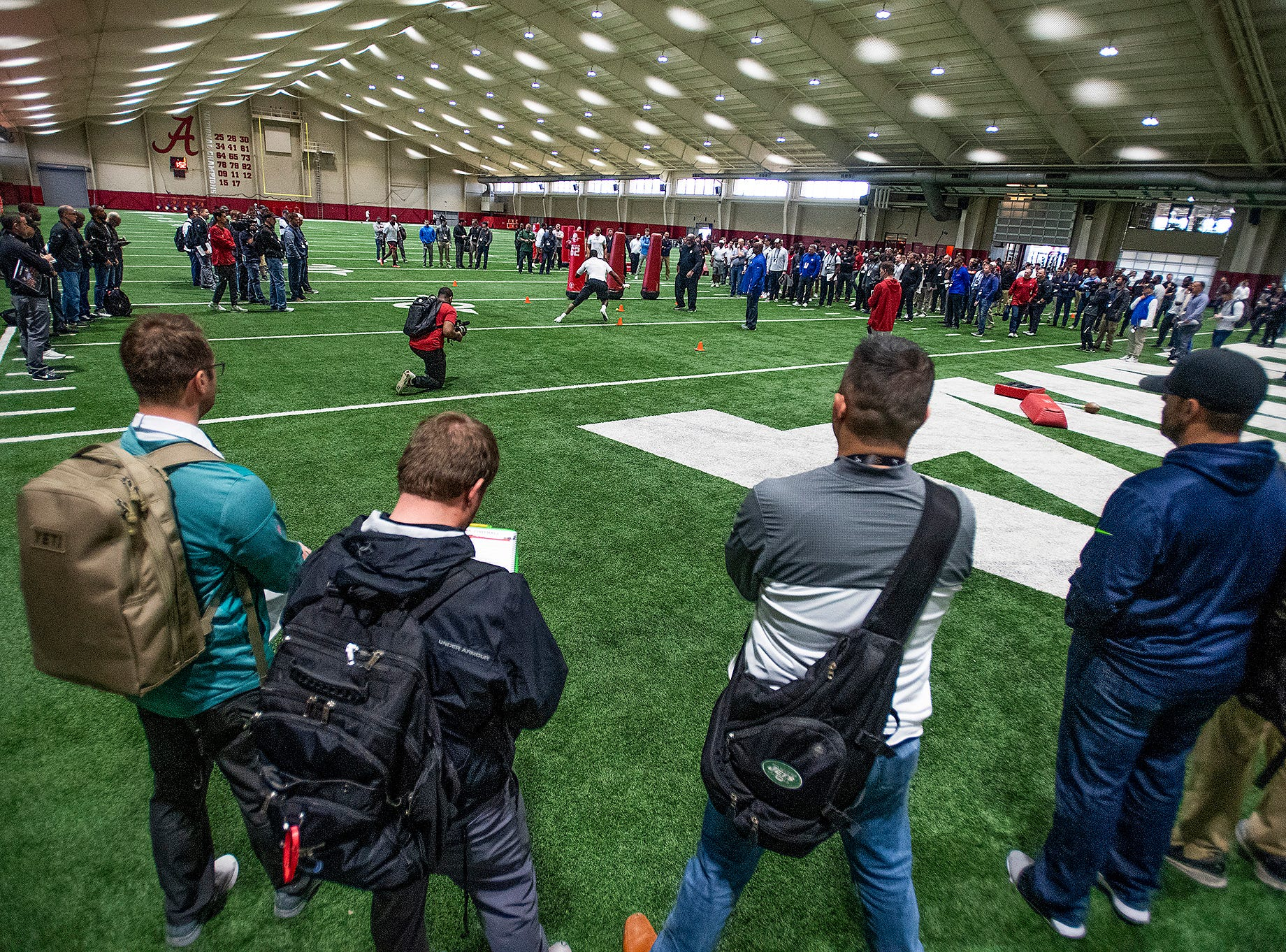 NFL scouts watch Alabama players run drills during Pro Day on the University of Alabama campus in Tuscaloosa, Ala., on Tuesday March 19, 2019.