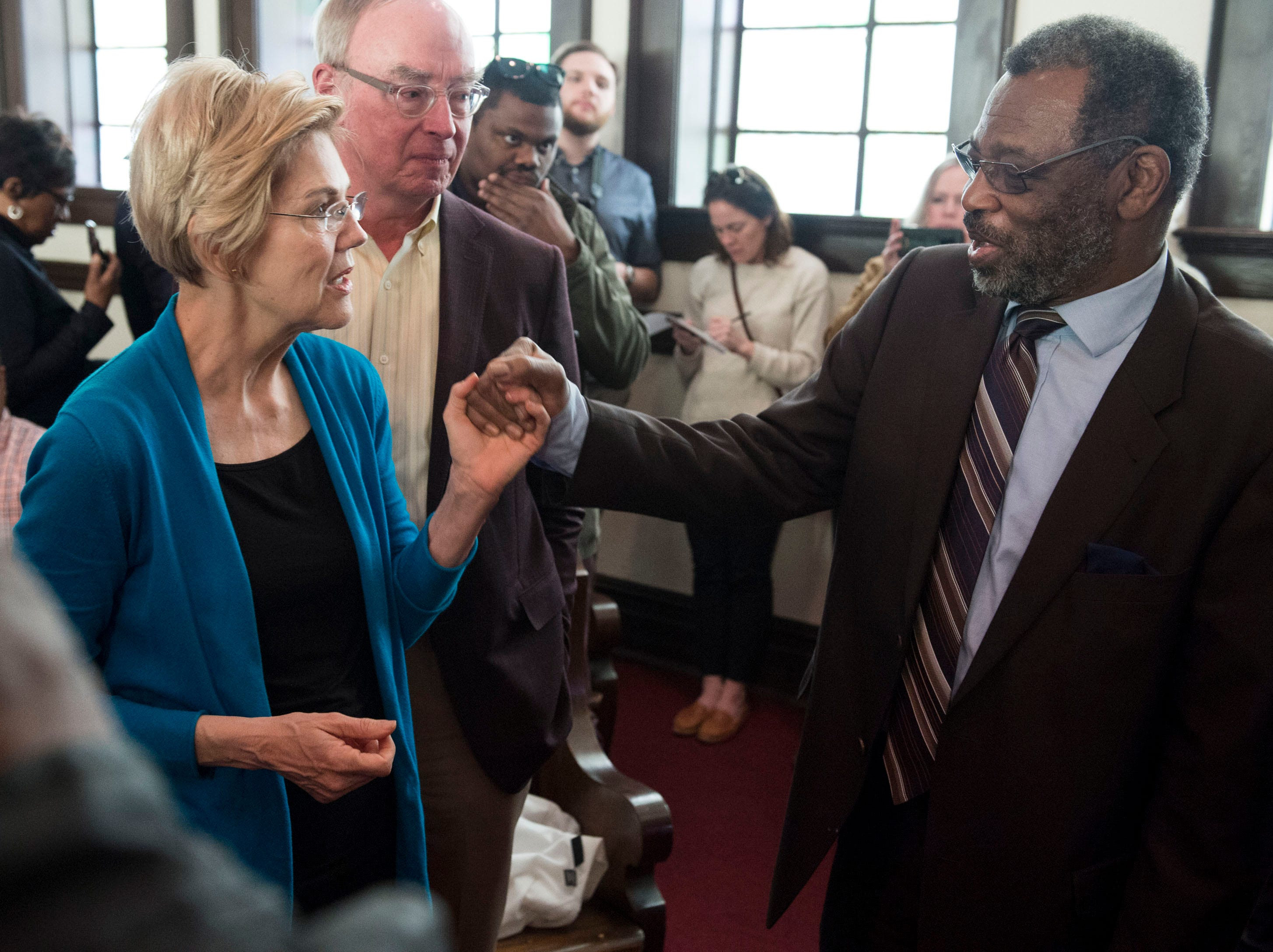 Sen. Elizabeth Warren holds hands with Pastor Leodis Strong at Brown Chapel AME Church in Selma, Ala., on Tuesday, March 19, 2019.