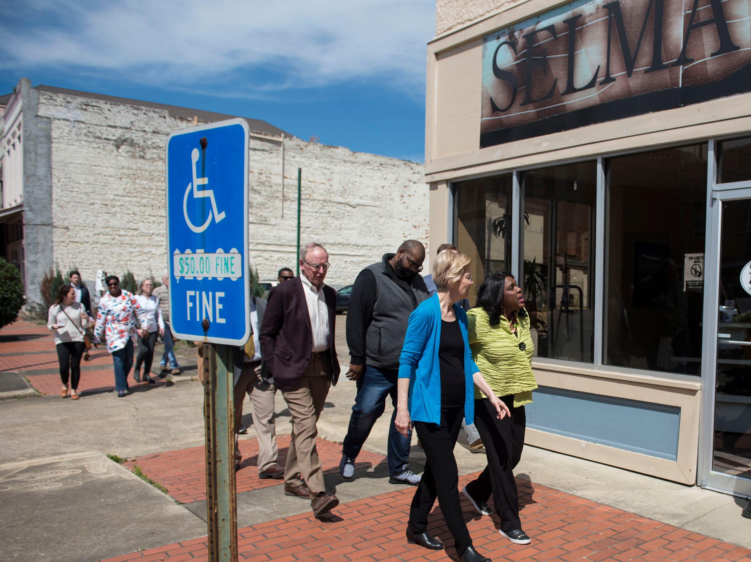 Sen. Elizabeth Warren, left, and Rep. Terri Sewell walk the streets of downtown Selma, Ala., on Tuesday, March 19, 2019.