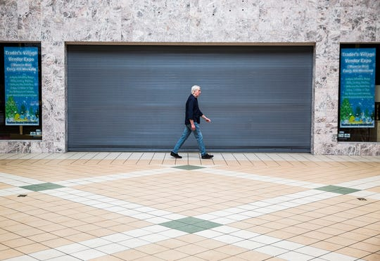 A man walks past the former site of Carson's at the Muncie Mall.