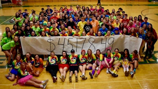 Yorktown students pose with the paper which revealed their fundraising total for their 2019 Dance Marathon.