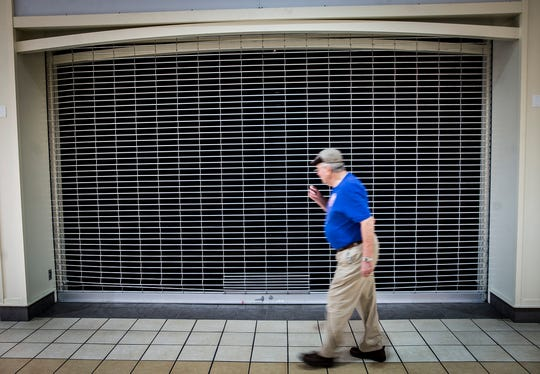 A security gate blocks off an empty space at the Muncie Mall Tuesday.