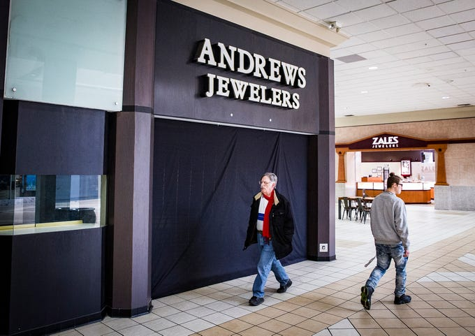 Walkers pass the former site of Andrews Jewelers at the Muncie Mall.