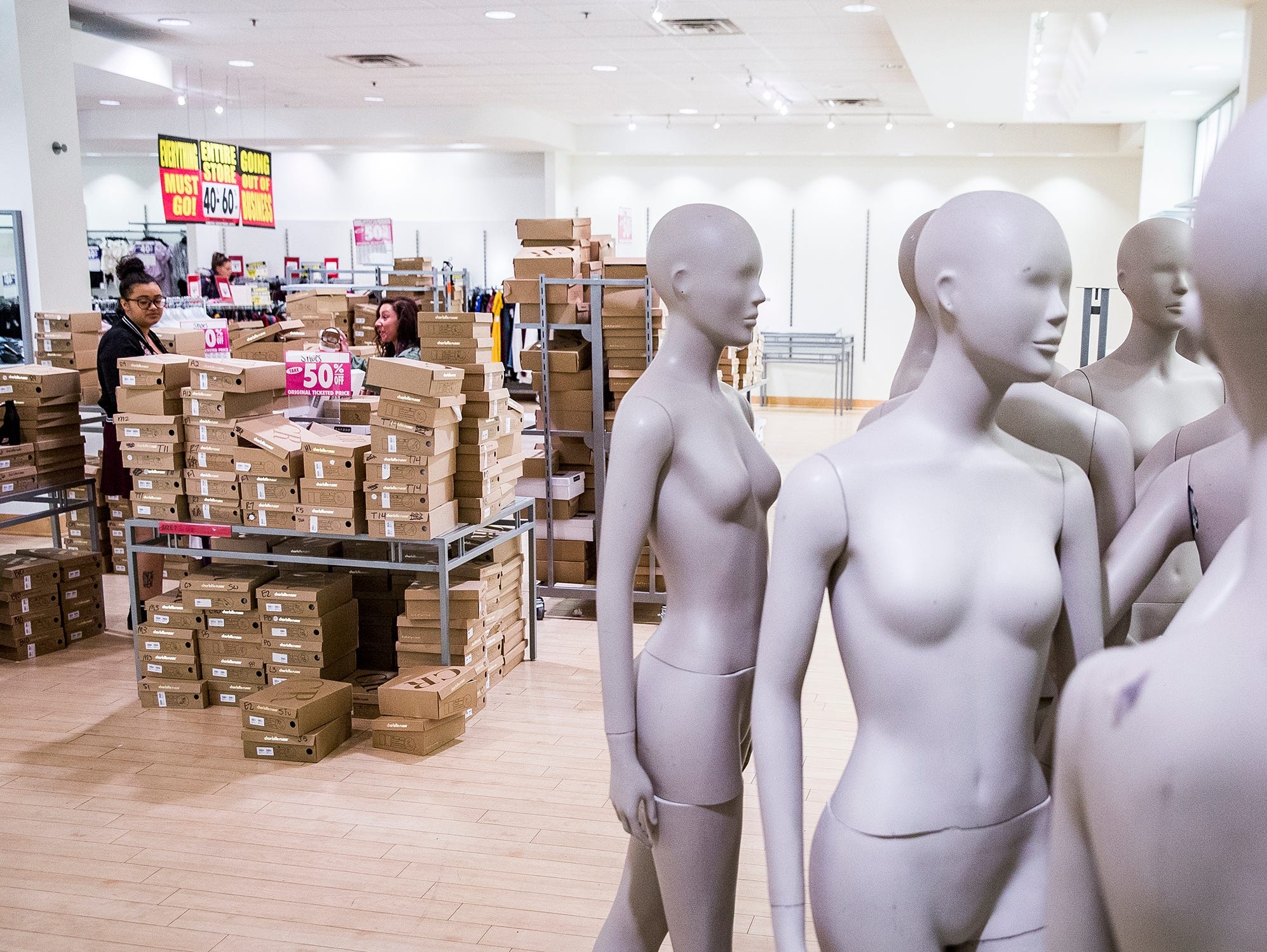 Mannequins are prepared for removal from Charlotte Russe during a store closing sale at the Muncie Mall Tuesday morning.