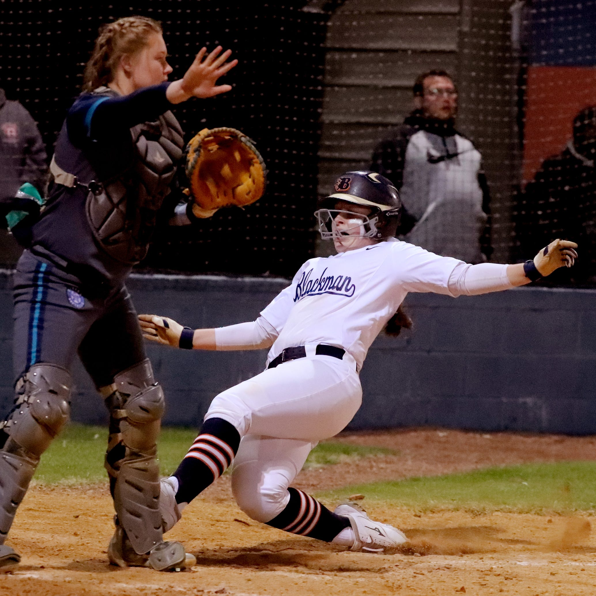 Blackman's Elaina McGill (16) slides safely into home to score a run as Siegel's Hannah Milhorn (4) waves off the throw, on Monday, March 18, 2019, at Blackman.