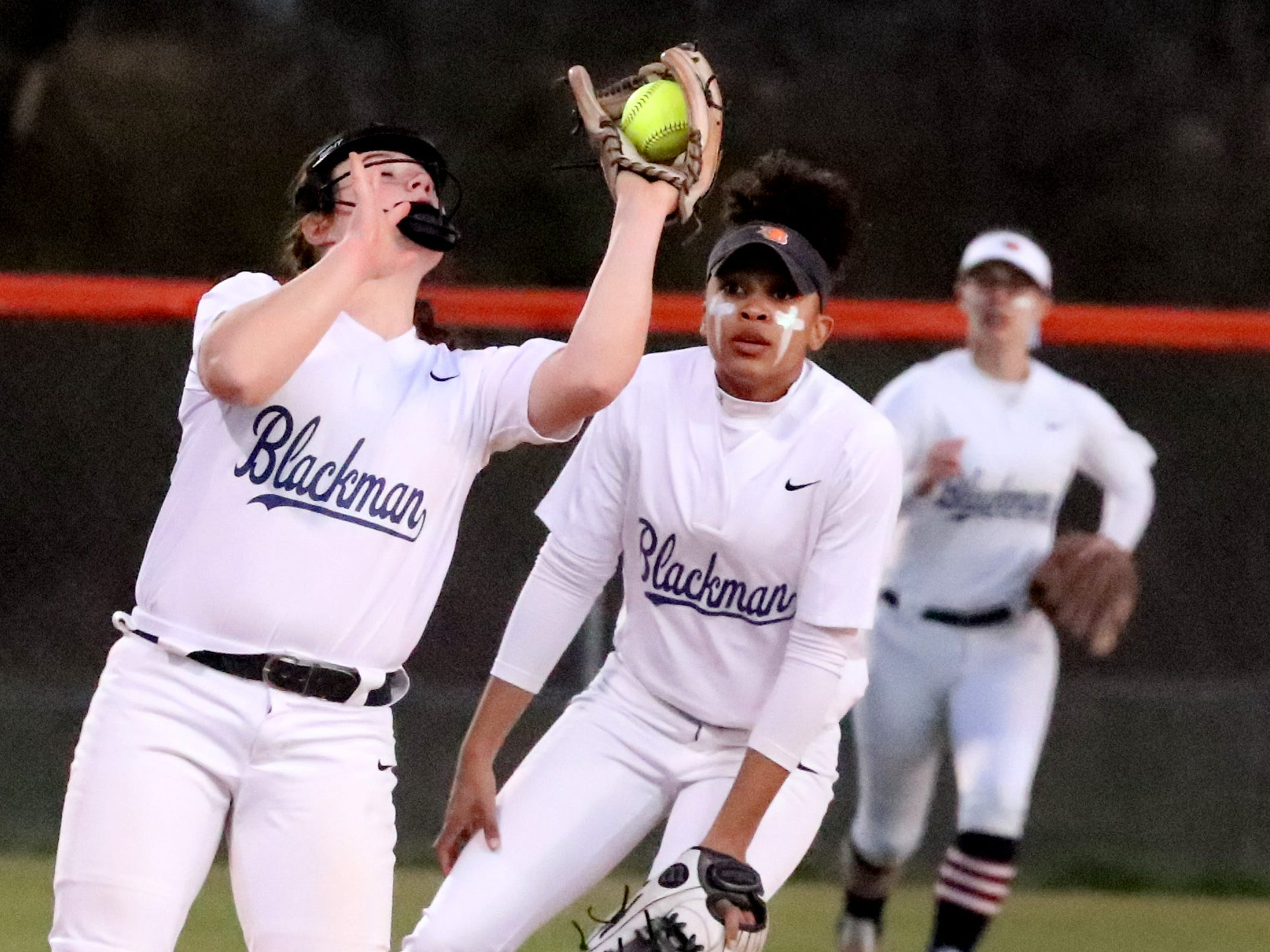 Blackman's Killian Roberts (24) makes a catch  and an out against Siegel, as Blackman's Kalei Harding (8) watches her, on Monday, March 18, 2019, at Blackman.