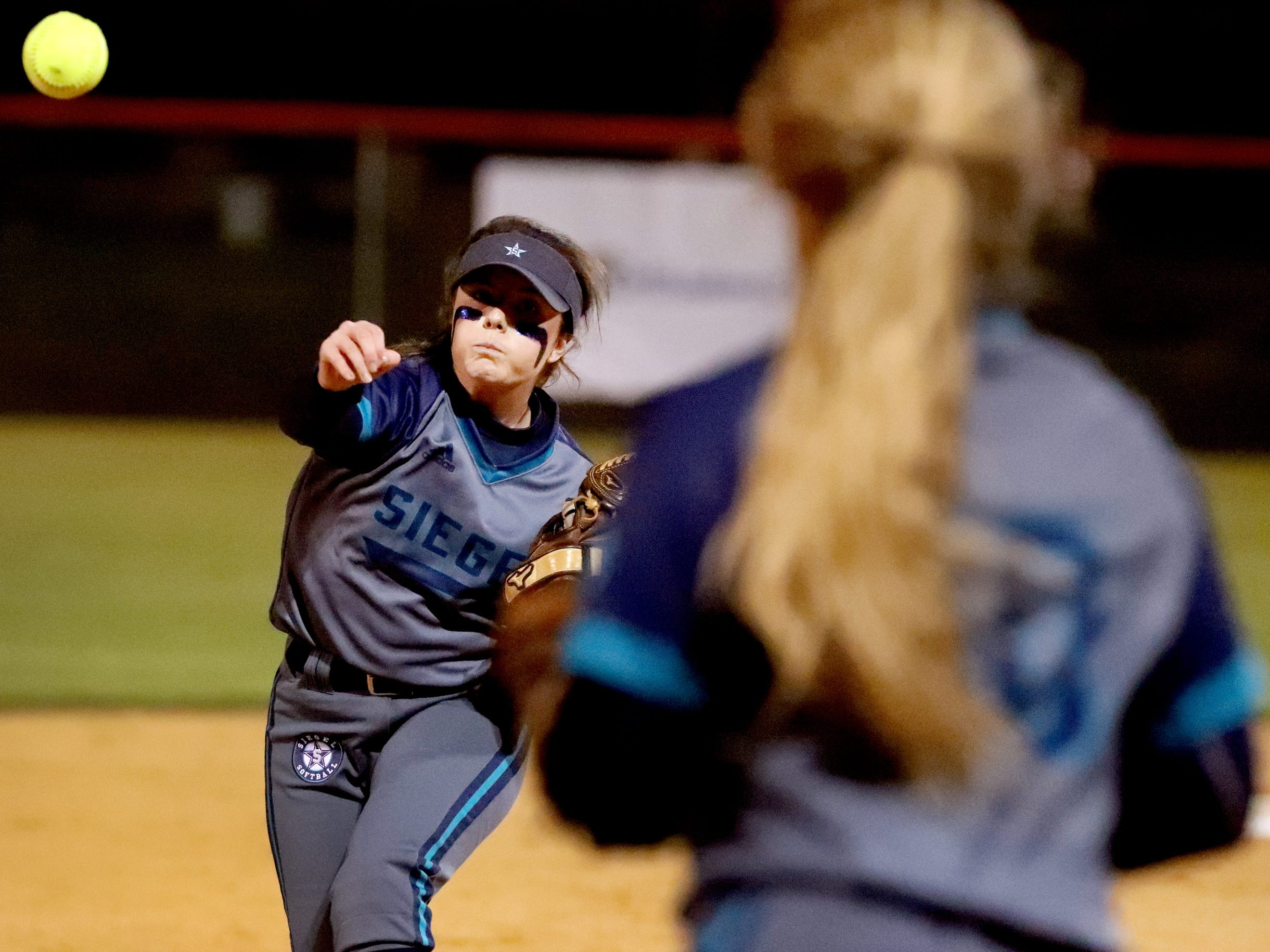 Siegel's Vanessa Westfall (3) tosses the ball to third baseman Siegel's Caitlyn McCrary (10) to try and get Blackman's Alissa Hart (22) out, on Monday, March 18, 2019, at Blackman.