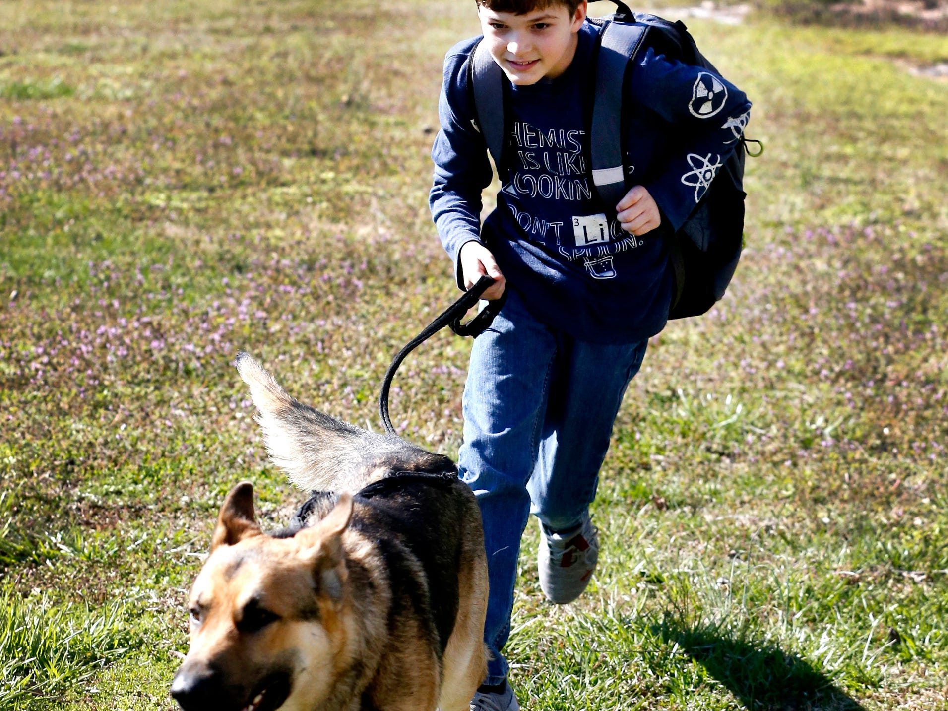 Justin White, 10, runs to his home with his dog Goblin, on Tuesday, March 19, 2019, after Goblin greeted him after getting off the school bus.