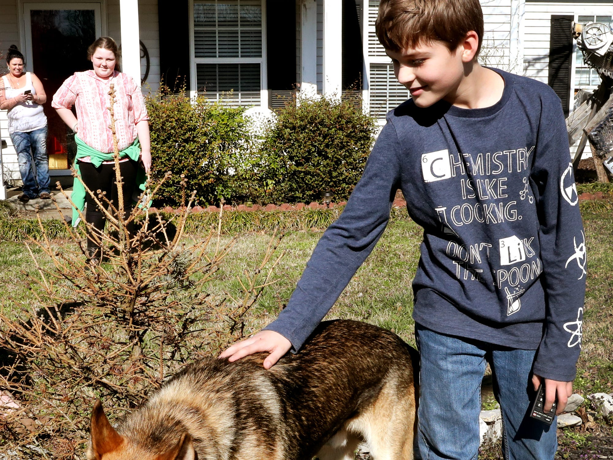 Justin White, 10, pets on his dog, Goblin, on Tuesday, after he was returned to the family's Christiana home on March 19, 2019, after officially being reported missing since March 10.