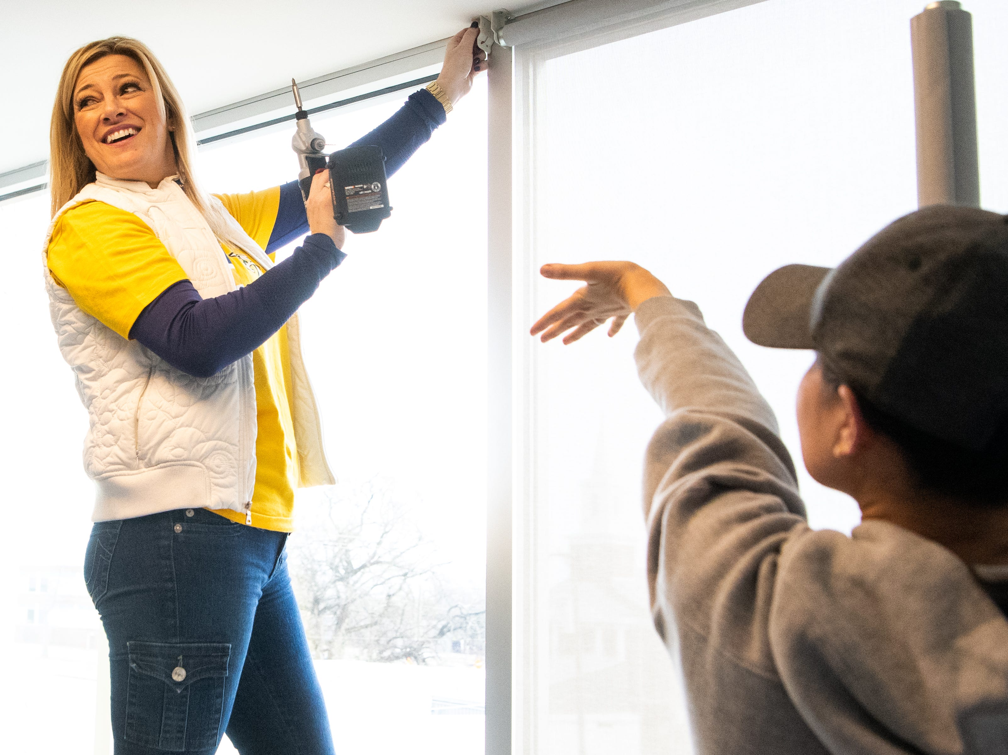 Kristen Laviolette hangs curtains in the entertainment room at Hope Lodge on Tuesday, March 12, 2019. As part of a room makeover, the significant others of Predators players and coaches painted walls, hung framed jerseys, brought in a huge entertainment center and spent two solid days enjoying time with each other.