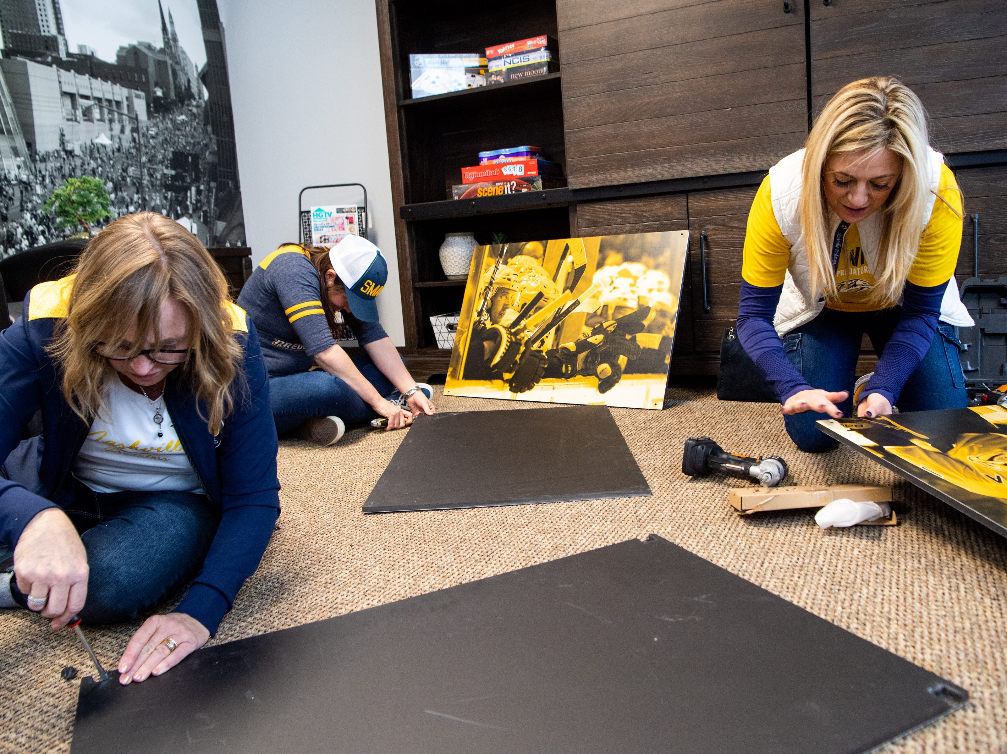 Rhonda McCarthy, Maureen Muse and Kristen Laviolette (from left) prepare photos to be hung to makeover the entertainment room at Memorial Foundation Hope Lodge as a project for the wives, girlfriends and fiancees of the Nashville Predators Tuesday, March 12, 2019, in Nashville, Tenn.