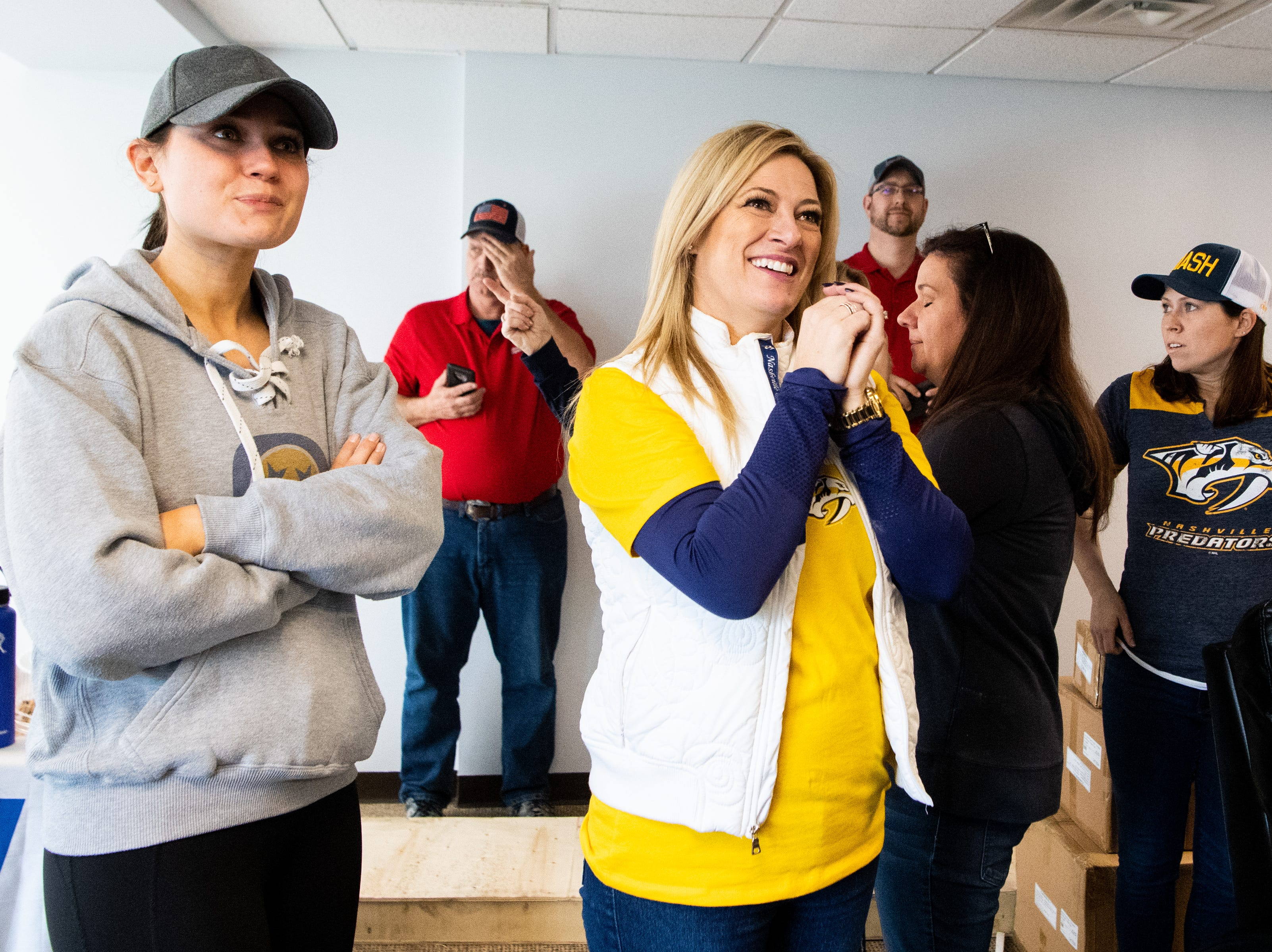 Kristen Laviolette and Kayla Price smile as they look at the new TV unit used in the makeover for the entertainment room at Memorial Foundation Hope Lodge as a project for the wives, girlfriends and fiancees of the Nashville Predators Tuesday, March 12, 2019, in Nashville, Tenn.