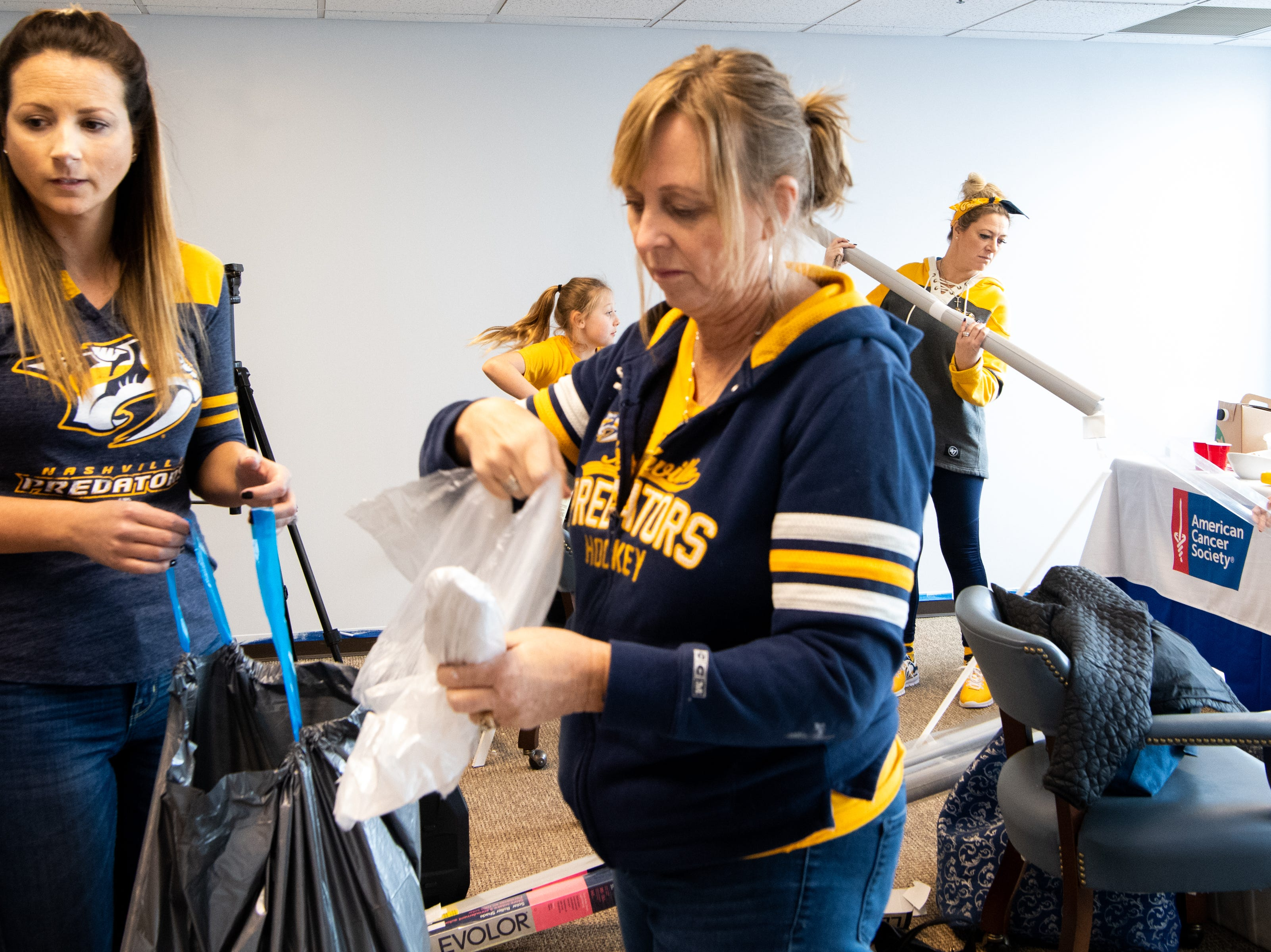 Marlene Vanderklok, Rhonda McCarthy, Kristen Laviolette and Rhonda McCarthy (from left) arrange materials to makeover the entertainment room at Memorial Foundation Hope Lodge as a project for the wives, girlfriends and fiancees of the Nashville Predators Tuesday, March 12, 2019, in Nashville, Tenn.
