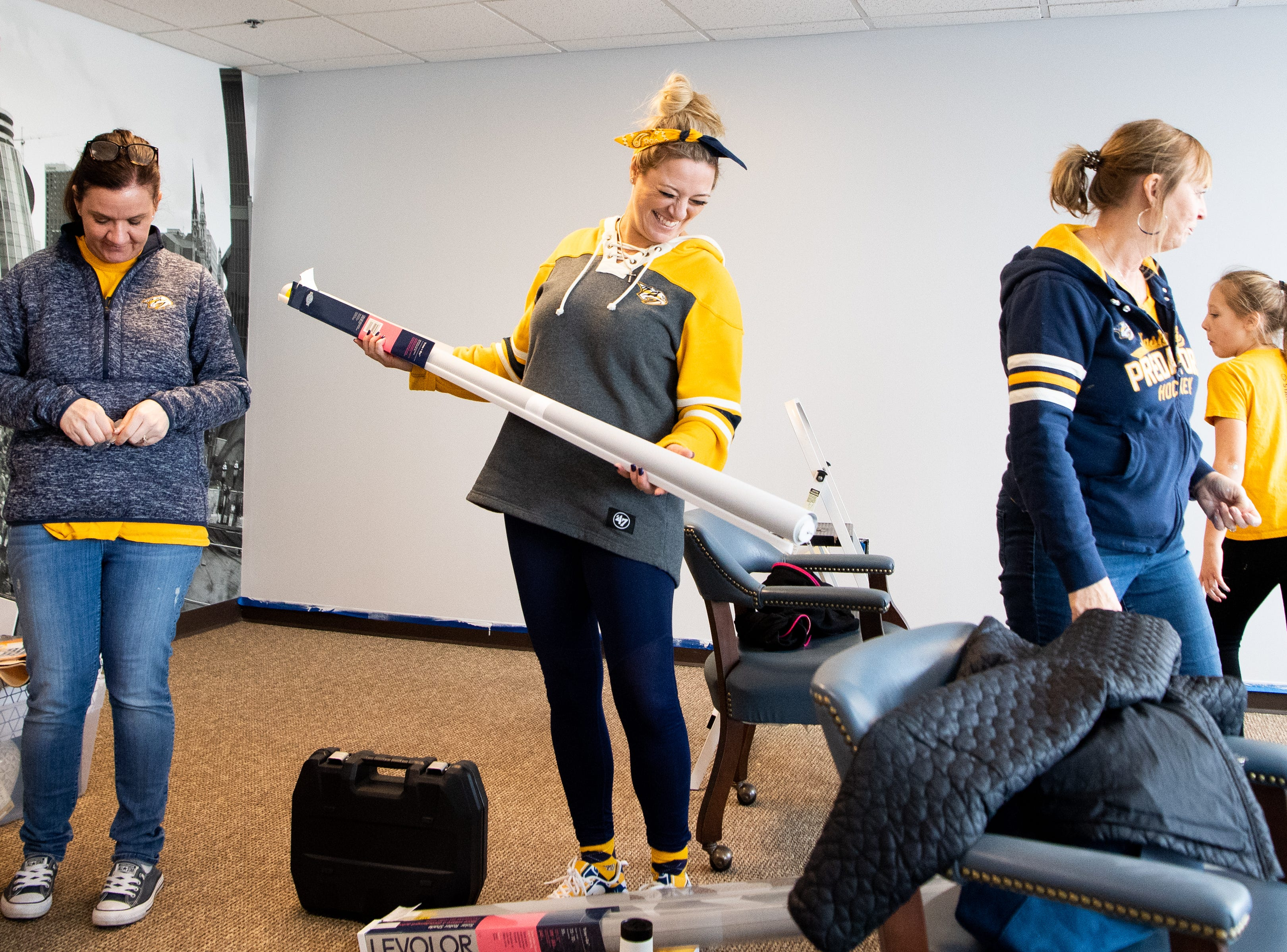 Tracey Henry, Kristen Laviolette and Rhonda McCarthy (from left) arrange materials to makeover the entertainment room at Memorial Foundation Hope Lodge as a project for the wives, girlfriends and fiancees of the Nashville Predators Tuesday, March 12, 2019, in Nashville, Tenn.