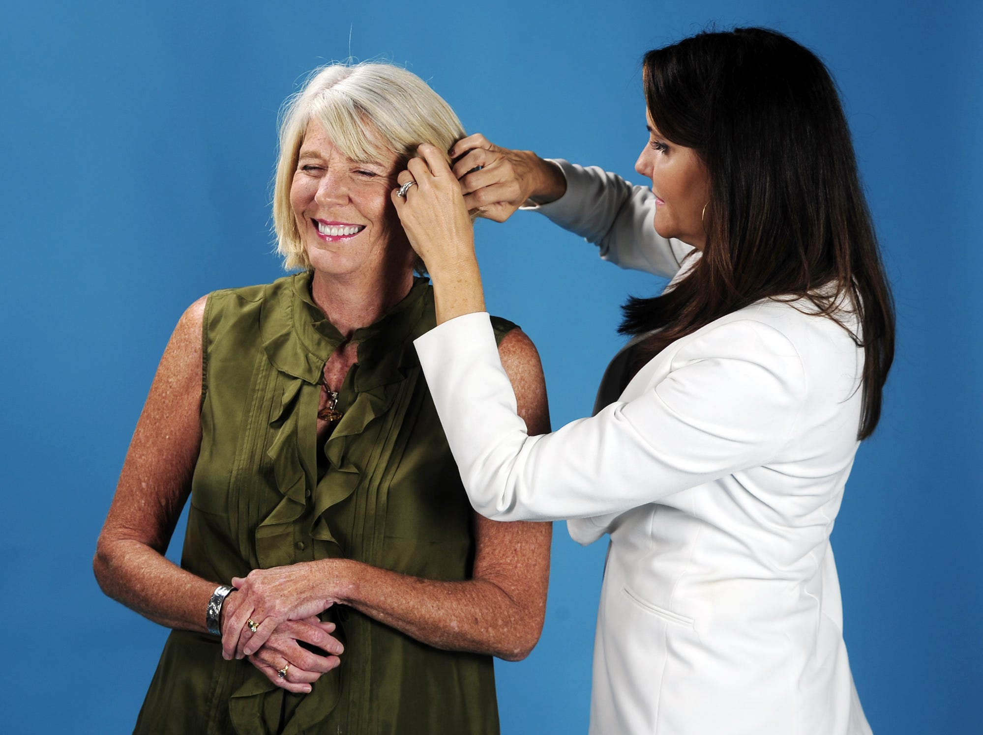 Cathi Aycock, right, works on the hair of fellow reporter Mary Hance, aka Ms. Cheap, in the studio Oct. 12, 2013, for their new column photos.