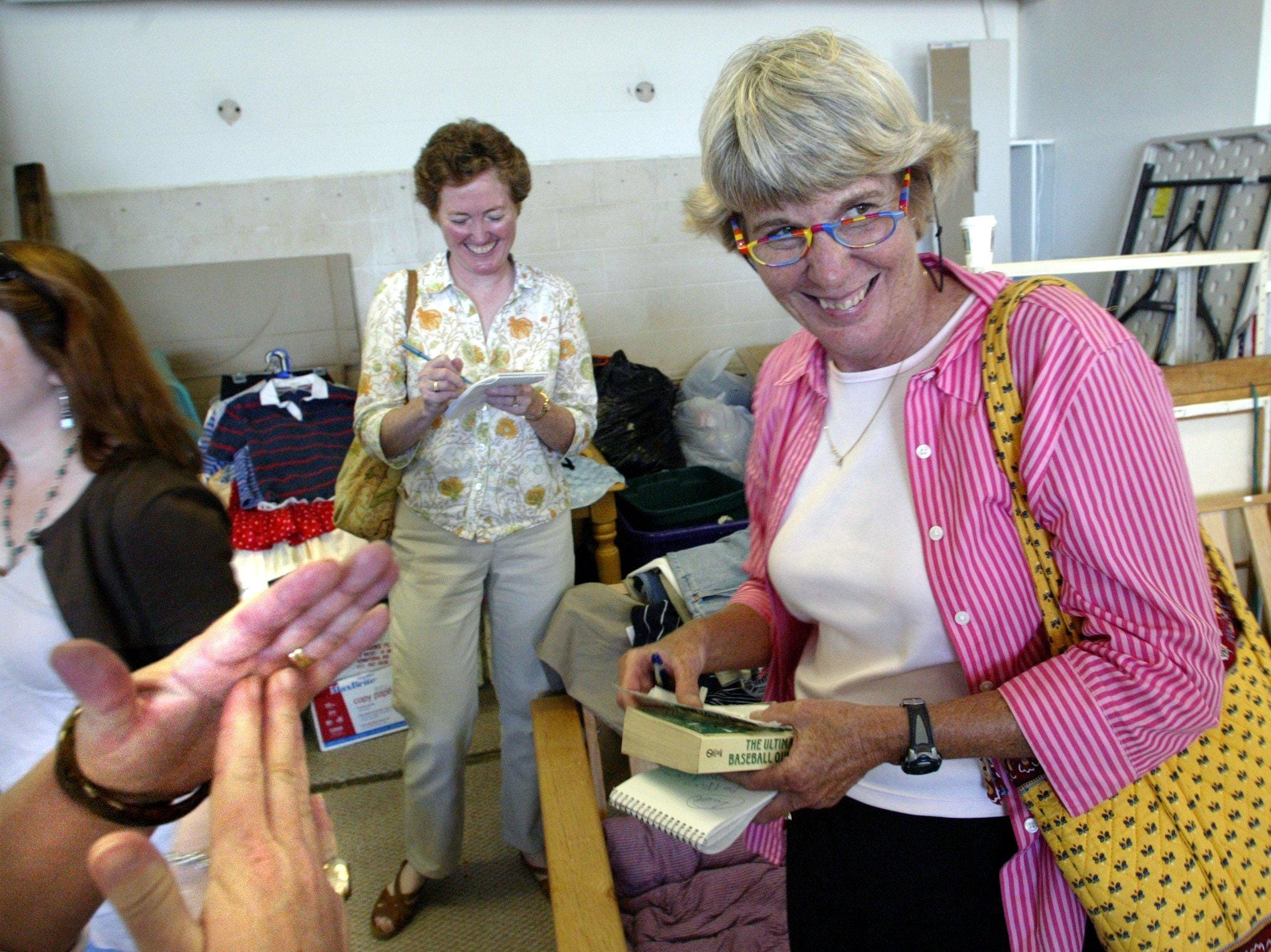 The Tennessean's Mary Hance, right, bargains with an employee at Our Thrift Store in Spring Hill on June 22, 2005, as reporter Sue McClure takes notes.