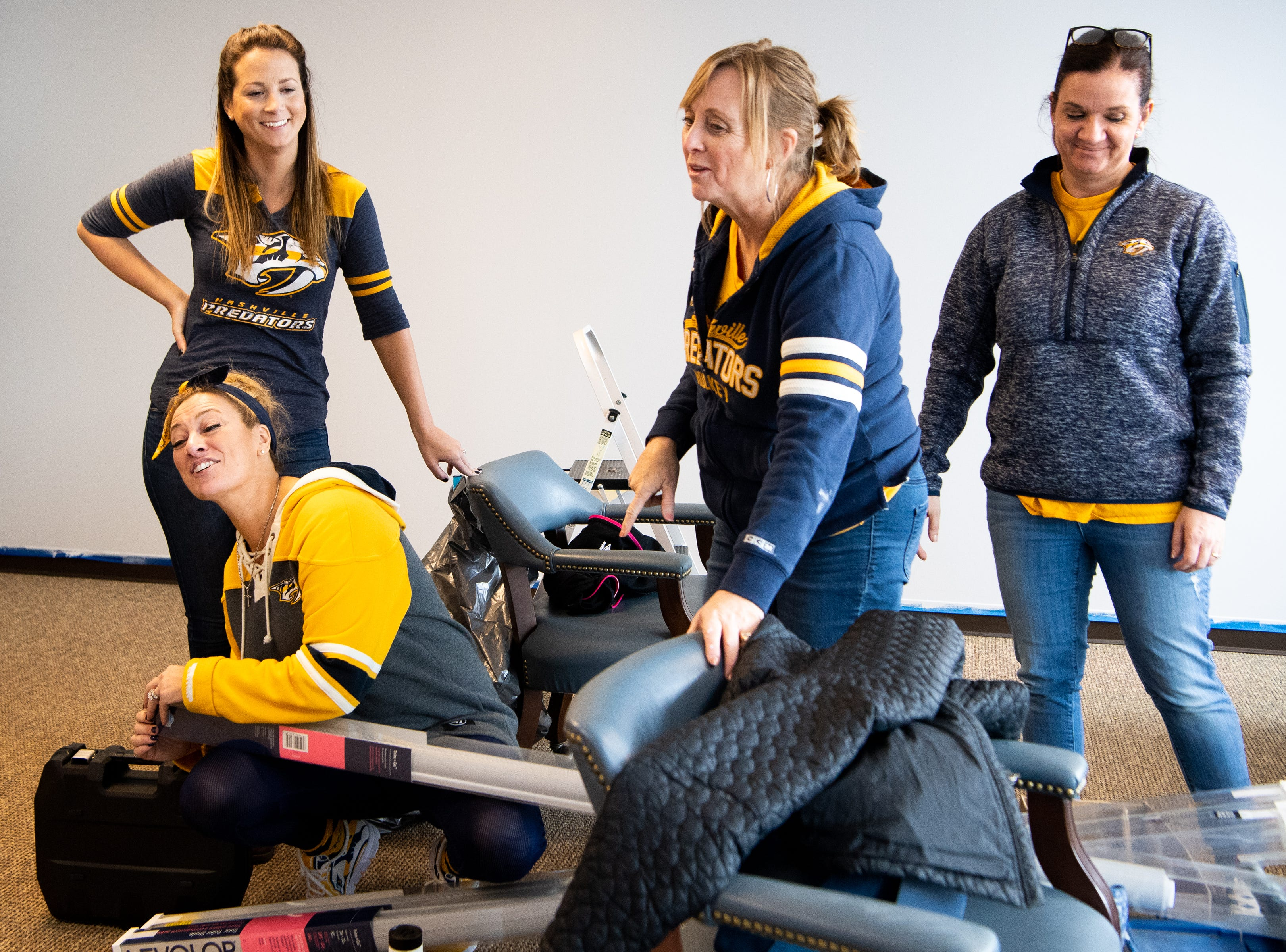 Kristen Laviolette (lower left), Marlene Vanderklok, Rhonda McCarthy, and Tracey Henry (from left) go through materials to makeover the entertainment room at Memorial Foundation Hope Lodge as a project for the wives, girlfriends and fiancees of the Nashville Predators Tuesday, March 12, 2019, in Nashville, Tenn.
