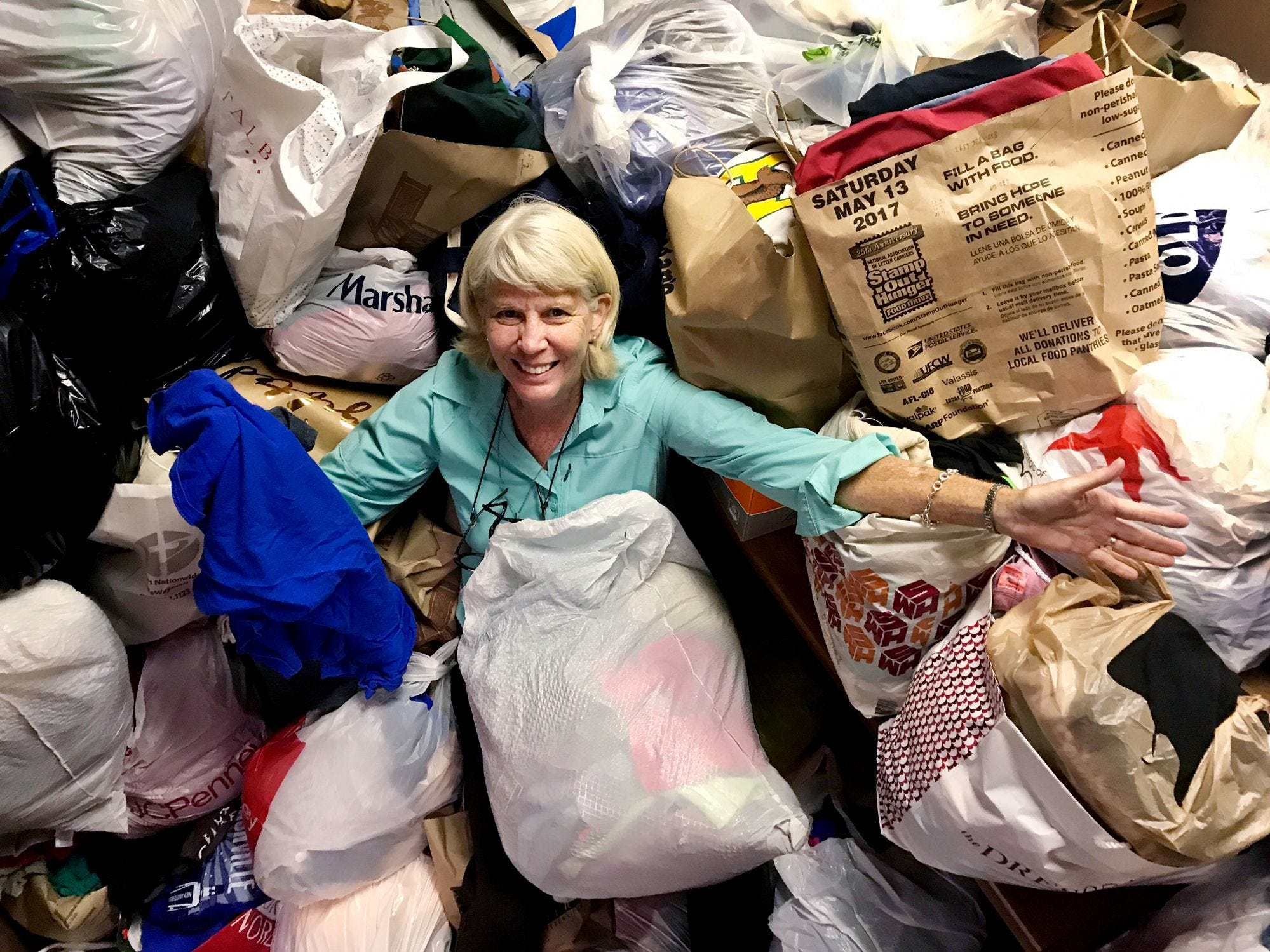 Mary Hance, aka Ms. Cheap, is happily buried in T-shirts that were donated for Ms. Cheap's T-shirt drive for Room in the Inn on June 18, 2017.