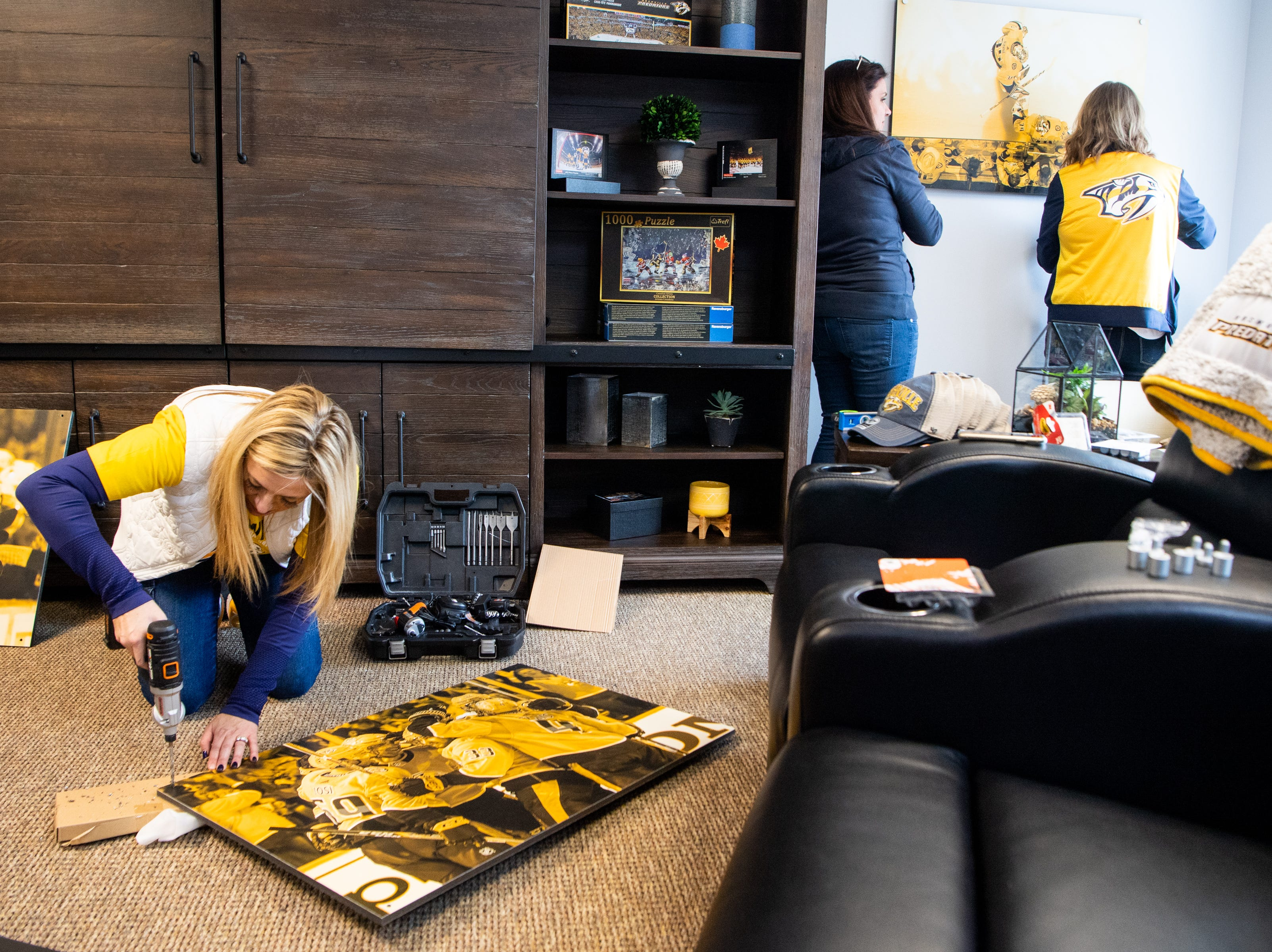 Kristen Laviolette drills holes in photos as part of a room makeover at Hope Lodge on March 12, 2019.