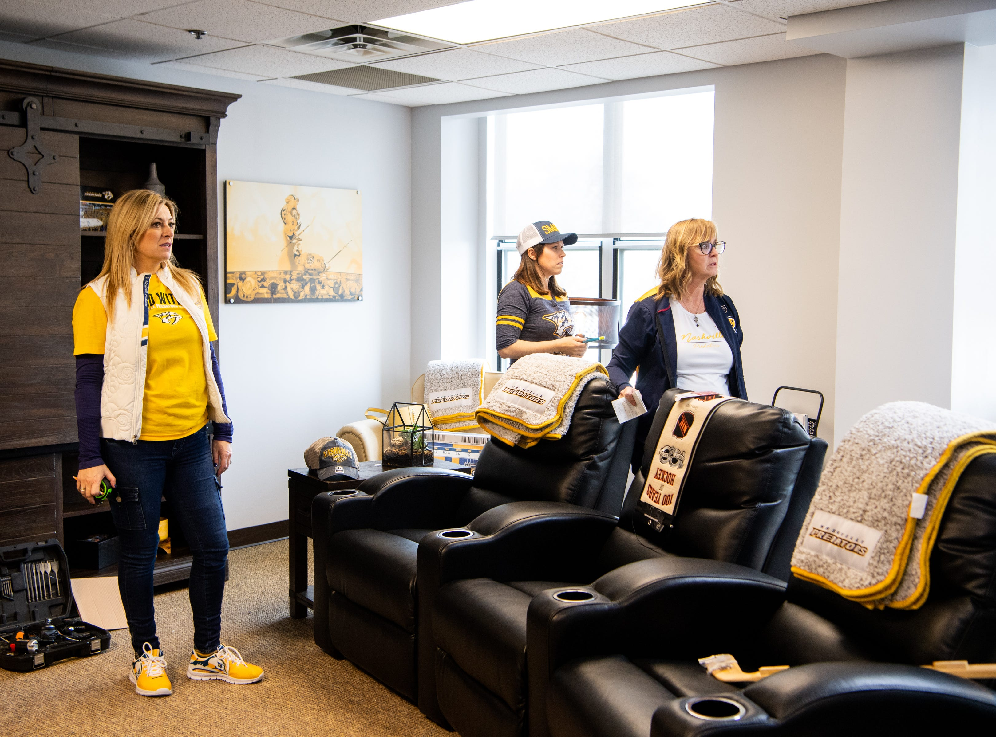 Kristen Laviolette, Maureen Muse and Rhonda McCarthy examine the hung photos while making over the entertainment room at Memorial Foundation Hope Lodge as a project for the wives, girlfriends and fiancees of the Nashville Predators Tuesday, March 12, 2019, in Nashville, Tenn.