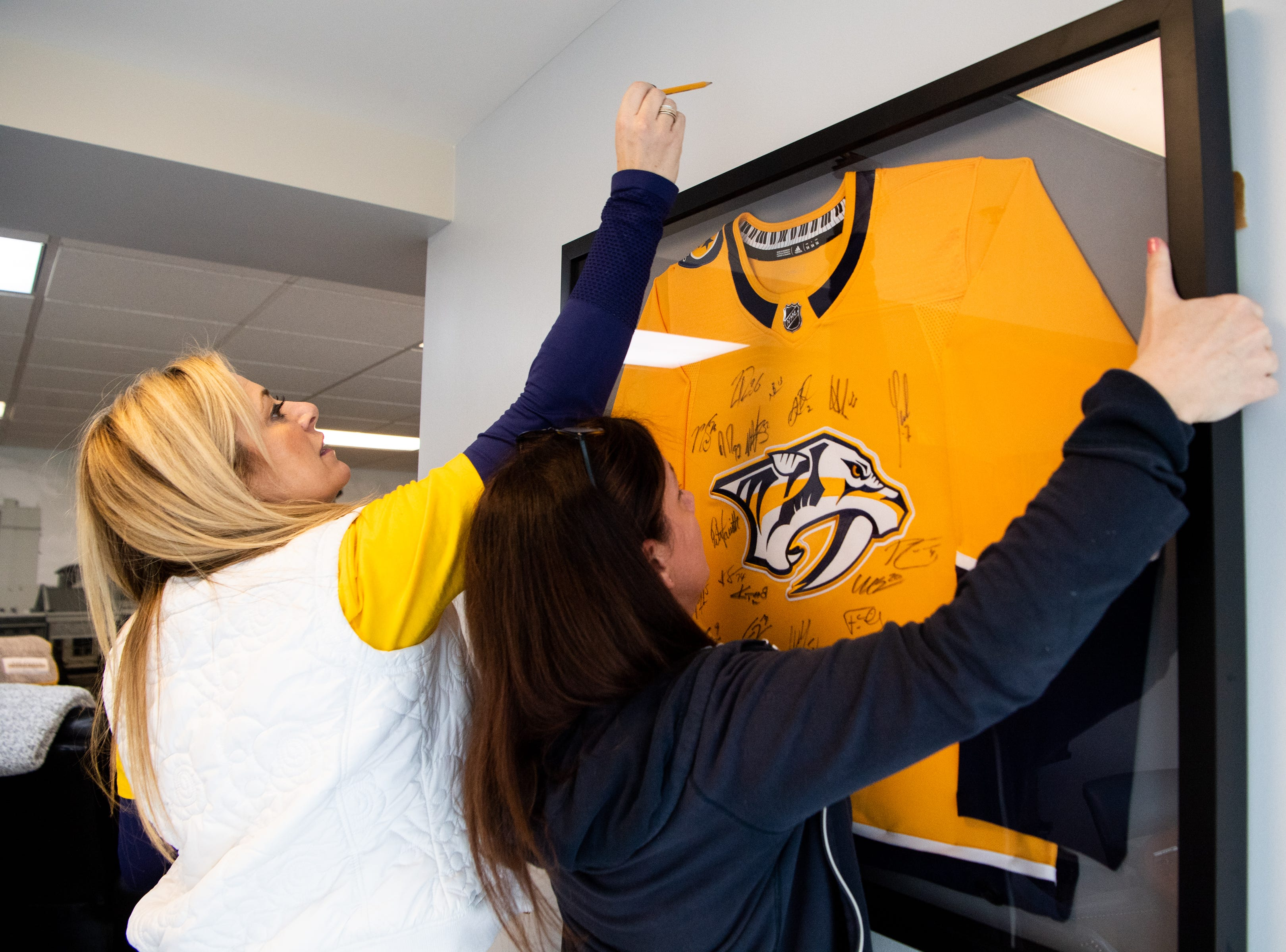 Kristen Laviolette and Tracey Henry hang an autographed Predators jersey as part of the makeover of the entertainment room at Hope Lodge on March 12, 2019.