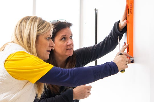 Kristen Laviolette, wife of the Predators' coach, and Tracey Henry, wife of the Predators' CEO, use a level to hang photos at Hope Lodge on Tuesday, March 12, 2019.