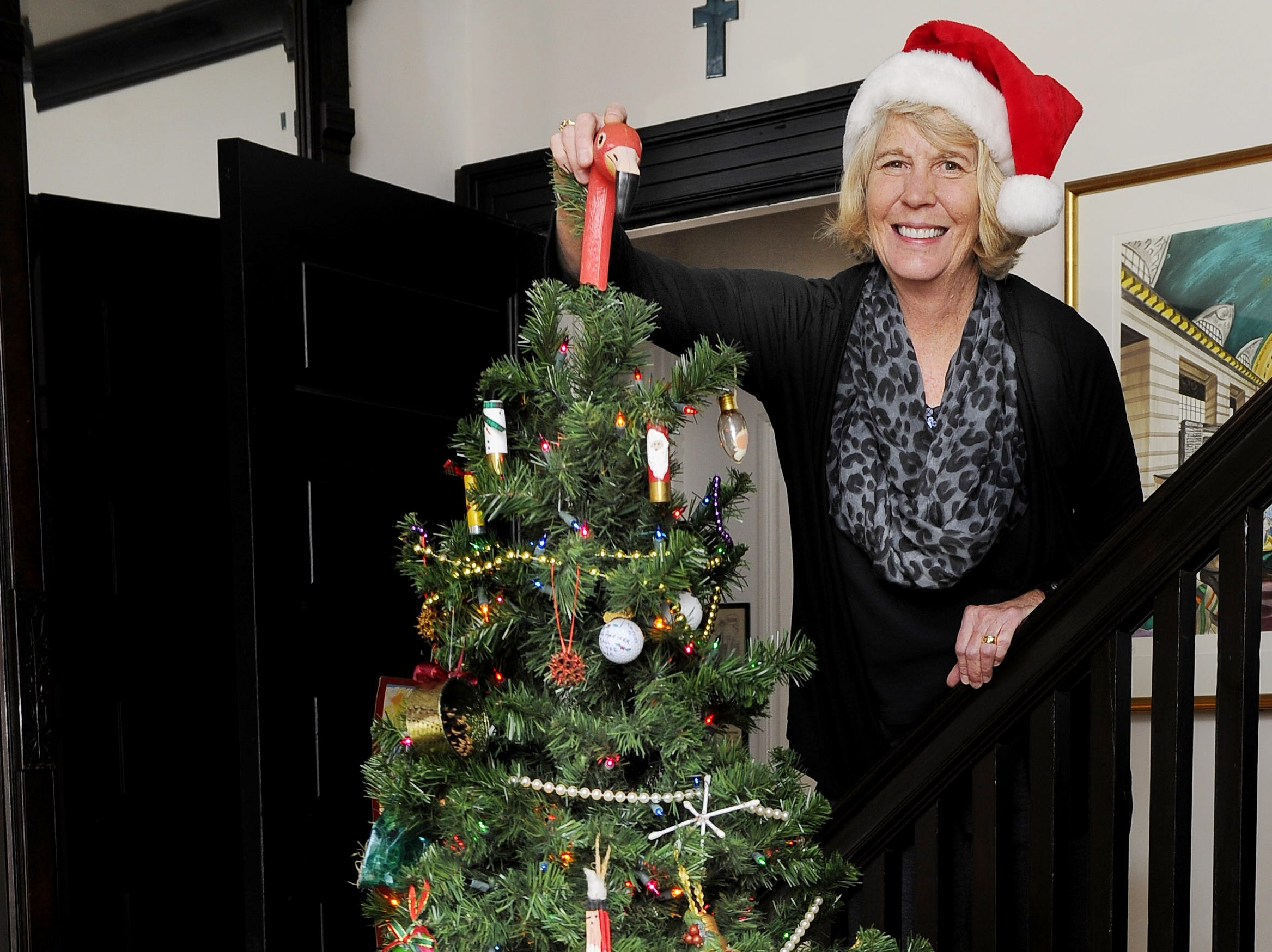 """Mary Hance's Ms. Cheap poses with her """"Cheap Christmas tree"""" on Dec. 12, 2013."""