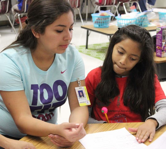 Miranda Herrera tutoring young Immokalee Reader Selest Martinez.