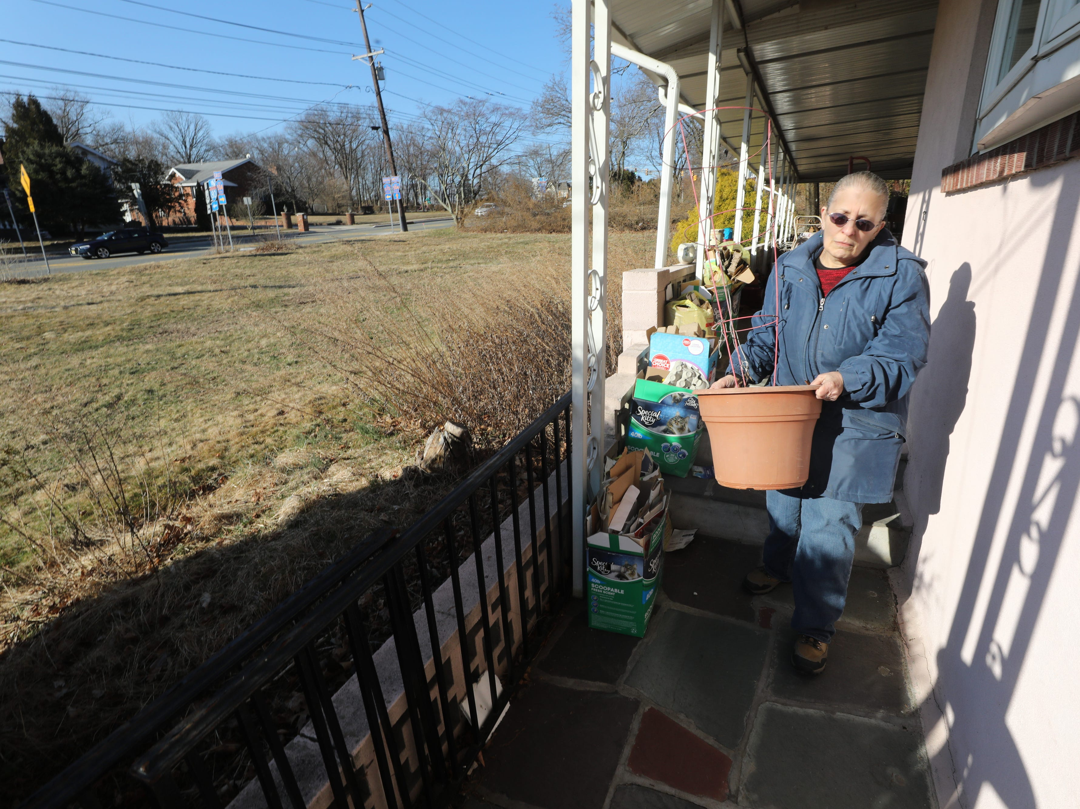 Madeline D'Alessandro carries some of her belongings to her car as she clears out the house she and her brother are being evicted from on March 19, 2019, after failing to pay the mortgage for the past 10 years.