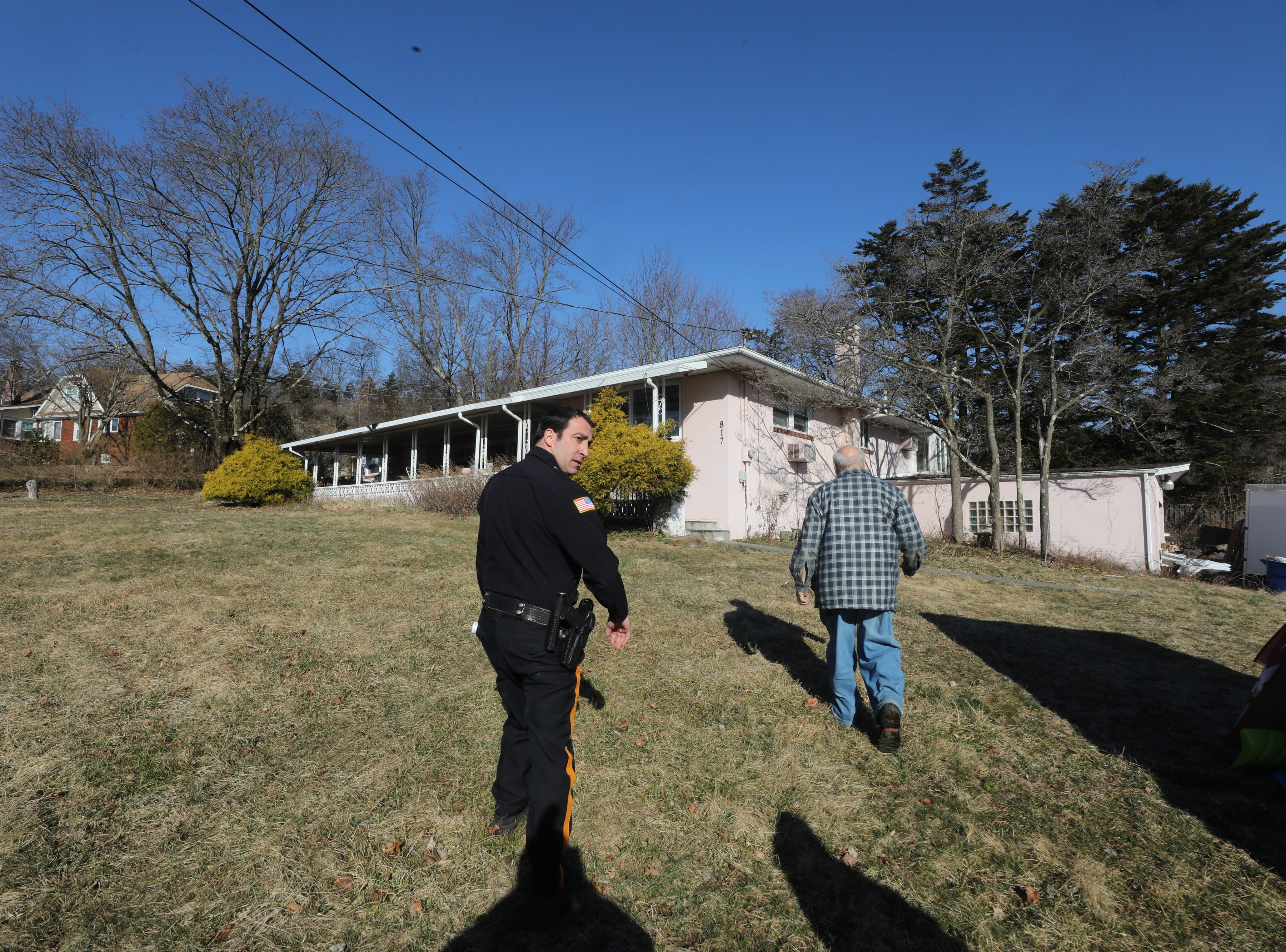 Passaic County Sheriff's Officer Nick D'Agostino and Charles D'Alessandro walk to D'Alessandro's home that he is being evicted from on March 19, 2019, after failing to pay the mortgage for the past 10 years.