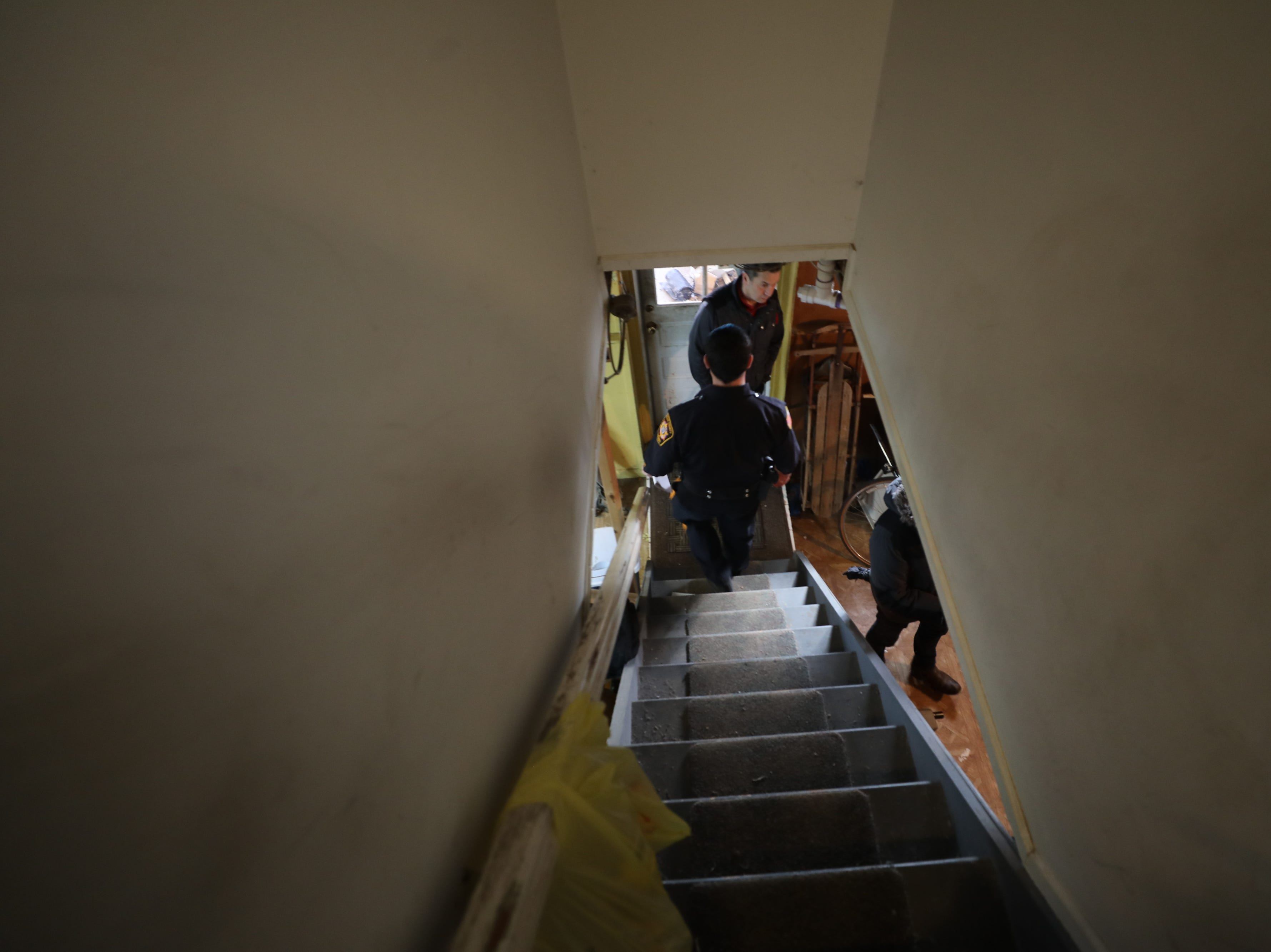 Sheriff's Officer Nick D'Agostini walks down the steps into the basement of the house occupied by Charles D'Alessandro and his sister. They are being evicted from the home on March 19, 2019, after failing to pay the mortgage for the past 10 years.