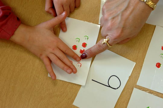 A teacher helps a kindergarten student count apple stickers on an index card.