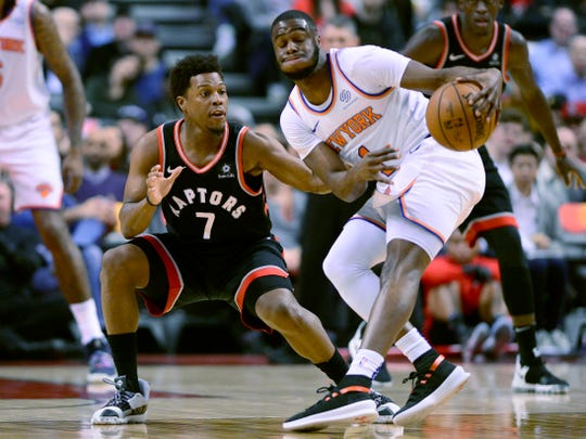 Toronto Raptors guard Kyle Lowry (7) and New York Knicks guard Emmanuel Mudiay (1) vie for control of a loose ball during first half NBA basketball action in Toronto, Monday, March 18, 2019. (Frank Gunn/The Canadian Press via AP)