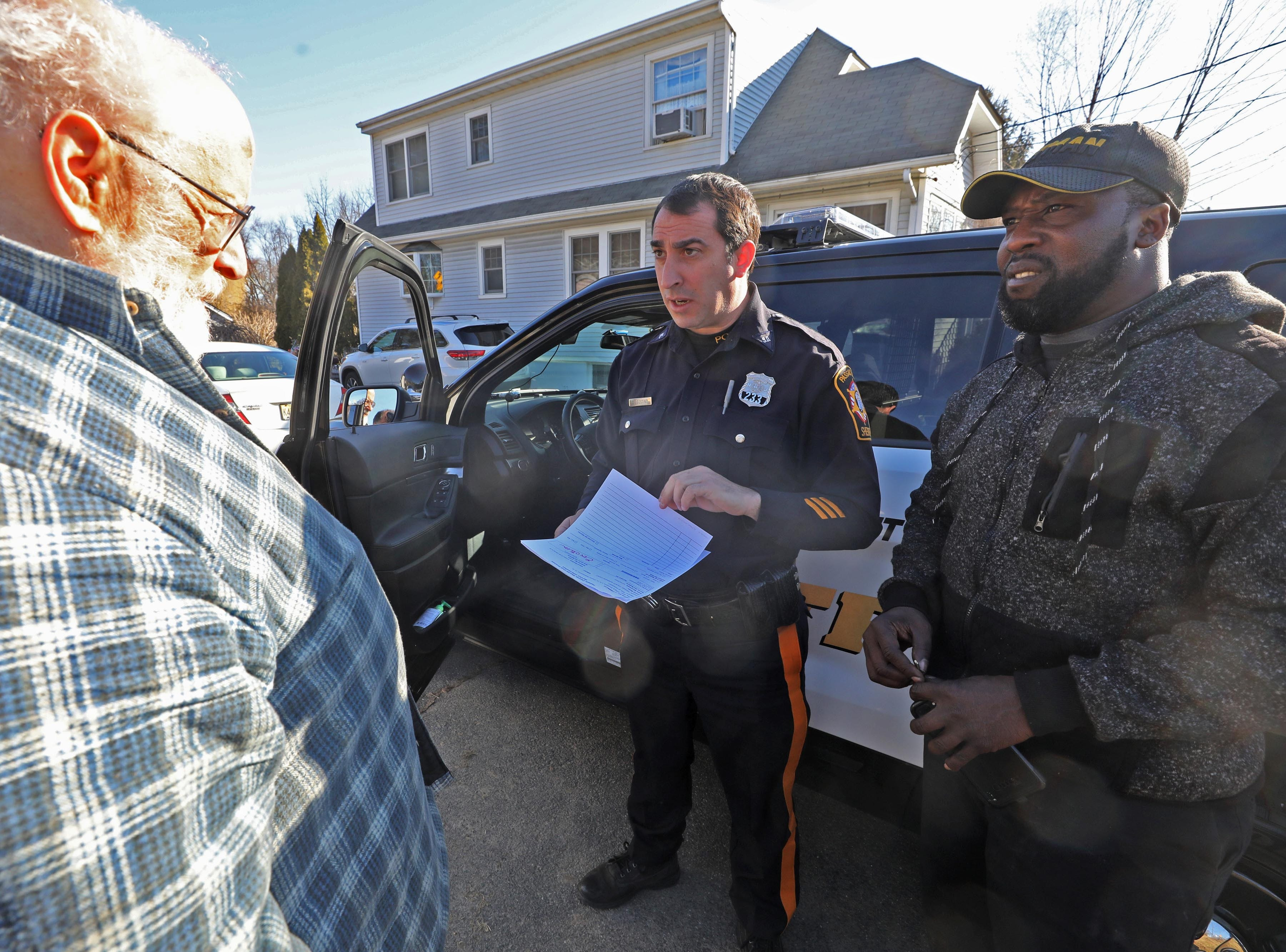 Charles D'Alessandro talks with Passaic County Sheriff's Officer Nick D'Agostino and a worker with the moving company as D'Alessandro is being evicted from his home on March 19, 2019, after failing to pay the mortgage for the past 10 years.