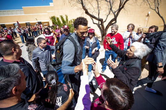 New Mexico State's Johnny McCants is greeted Tuesday, March 19, 2019, outside of the Pan American Center by Barbara Hubbard, longtime supporter of NMSU athletics and former special events director for the university. The men's basketball team left Tuesday for Salt Lake City, where they will play Auburn on Thursday in the NCAA Tournament.