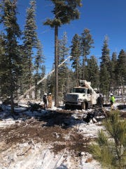 Linemen work to restore power after the March 13 wind storm knocked power out to residents in the mountain communities.
