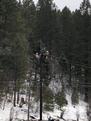 Linemen work to restore power to residents of several mountain communities after a wind storm knocked   power out.