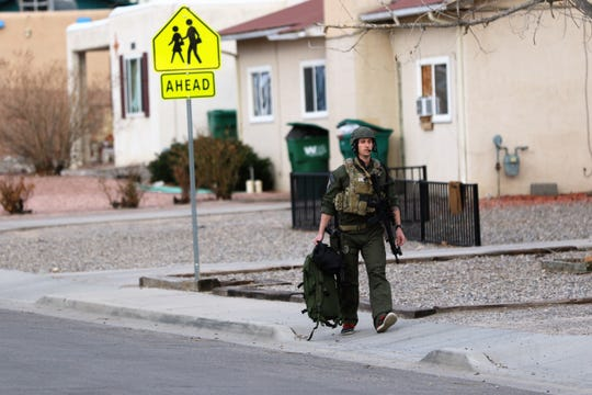 A member of the Farmington Police Department SWAT team walks along the 2900 block of Edgecliff Drive as an armed male suspect barricaded himself in a residence at 2906 Yale Drive Monday in Farmington.