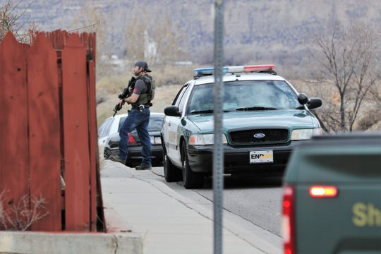An officer with a U.S. Marshals Service vest proceeds to a police standoff with an armed male suspect who was later found dead Monday night in a residence on Yale Drive in Farmington.