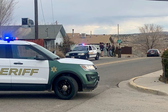 Residents near the scene of a police standoff with an armed man barricaded in a home are evacuated around 5:30 p.m. Monday as police moved a sniper into position and negotiators tried to get the man to surrender.