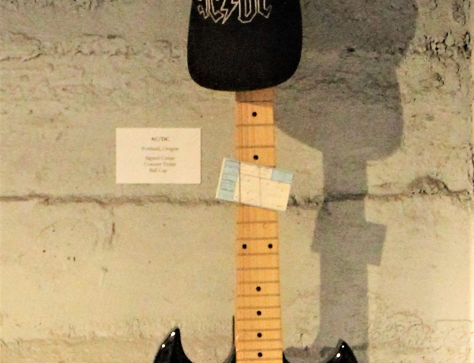 A signed AC/DC guitar and hat hangs on a wall at the Carrizozo Rock and Roll Hall of Fame.