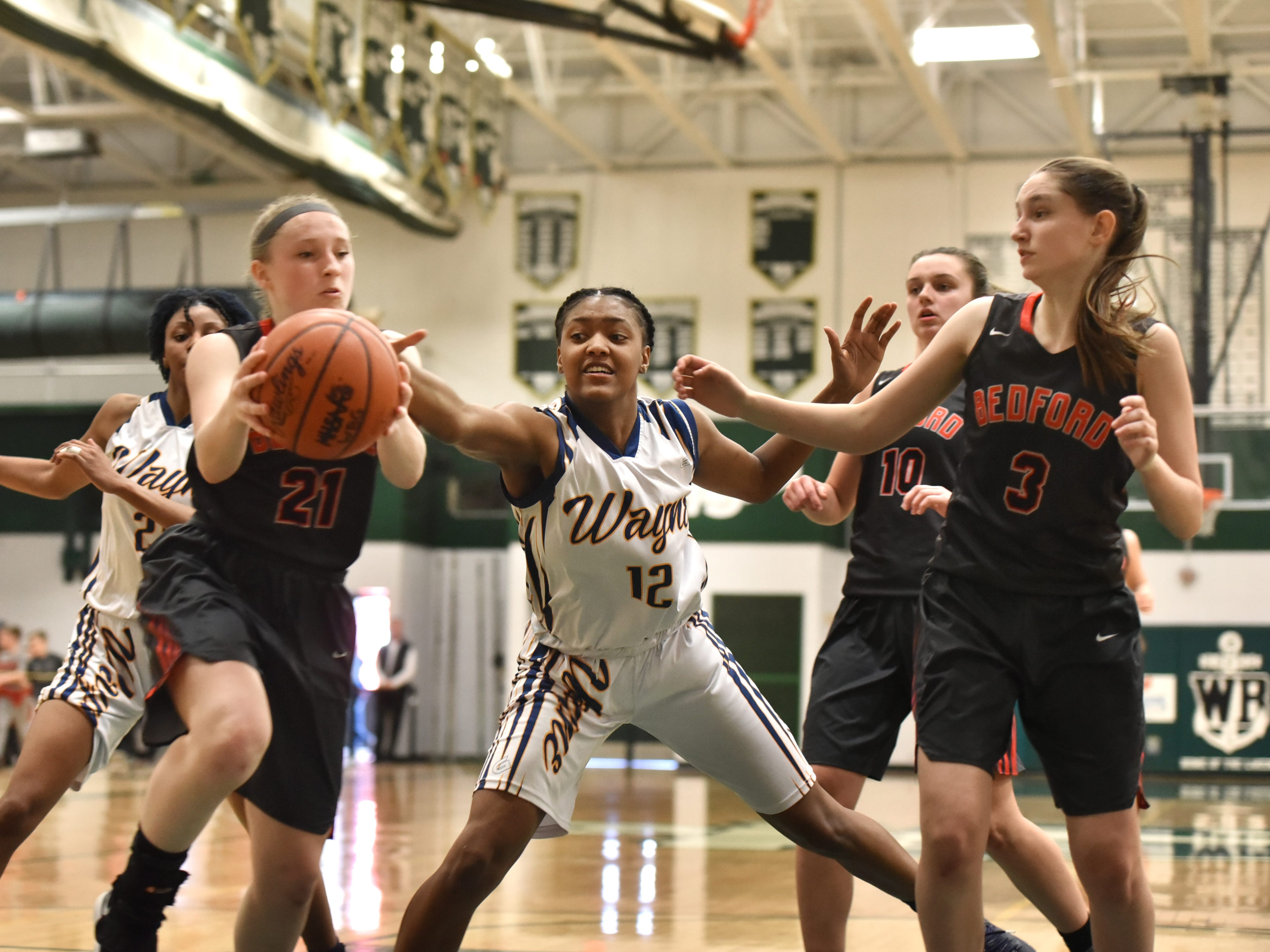 Zebra Jayah Hicks, center, tries to keep Temperance Bedford's Aubrie Zeunen from taking off with the basketball.