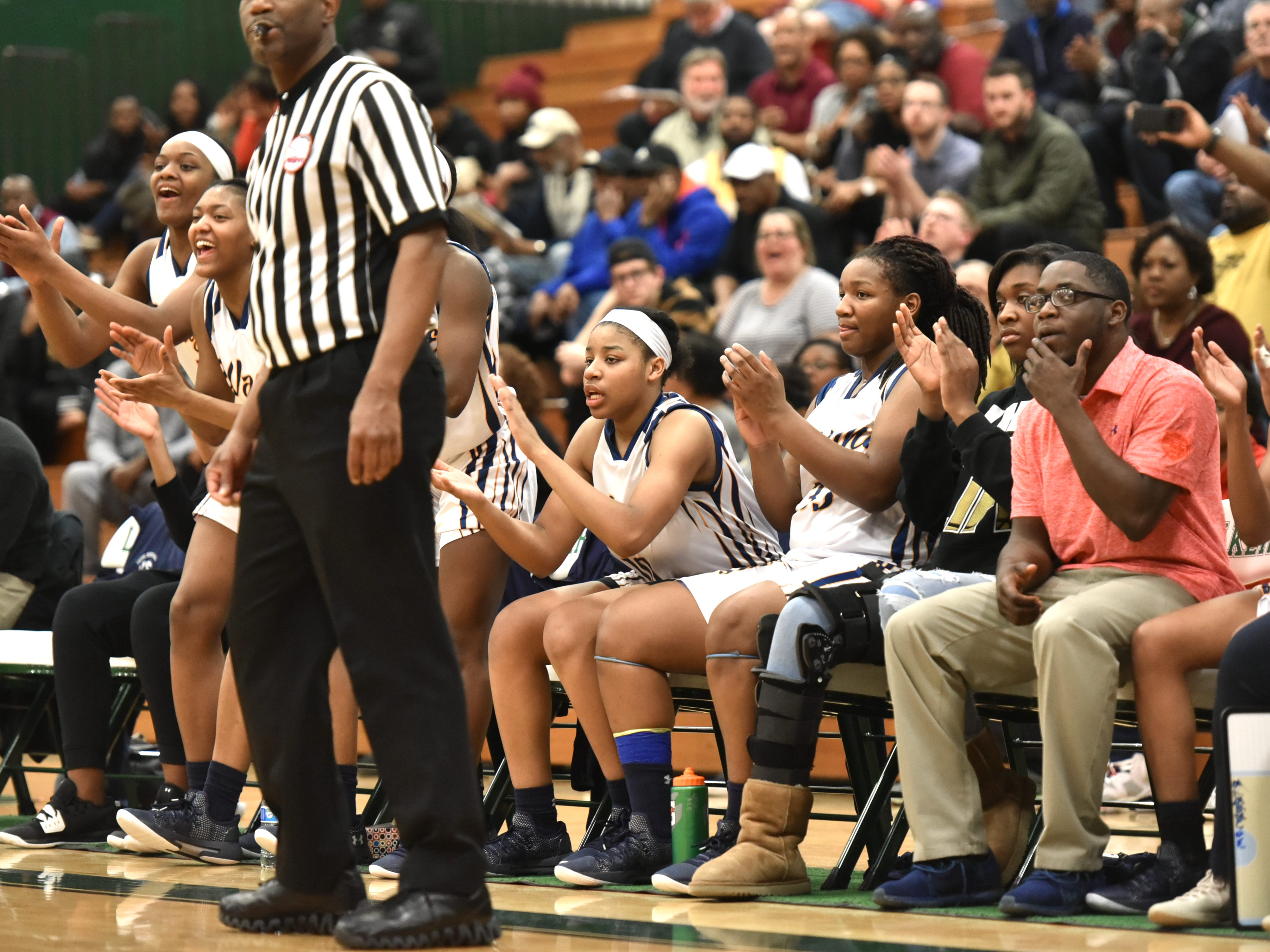 Late in the fourth, with most of the starters on the bench, the Wayne Memorial Zebras applaud the play of their teammates on the floor.
