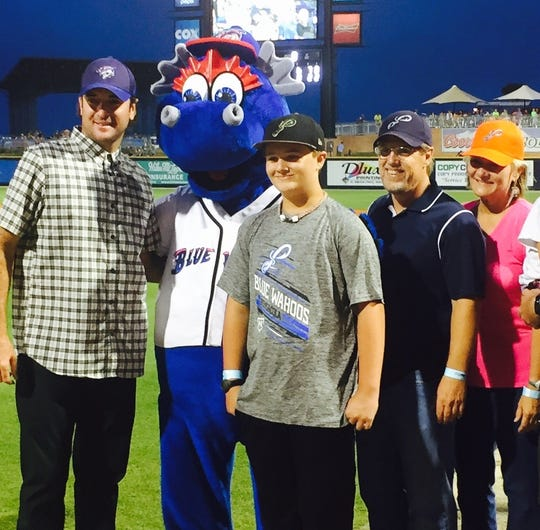 Caleb Summerlin, then 12, is joined by Bubba Watson, Blue Wahoos mascot Kazoo, and his parents after participating in the Home Run For Life moment on May 25, 2015 at Blue Wahoos Stadium.